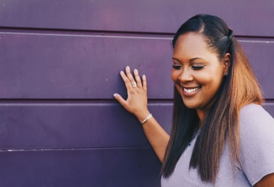 A woman with long dark hair looks downward, smiling and touching a purple wall