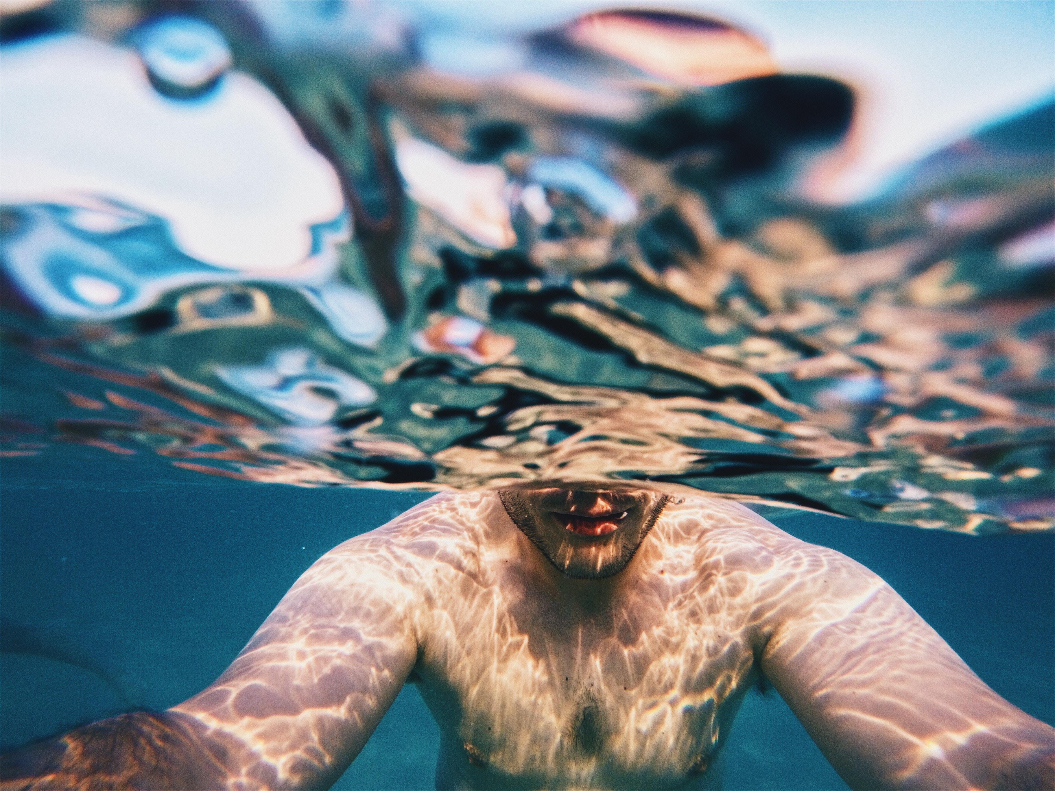 A half underwater shot of a man in Chaniotis.