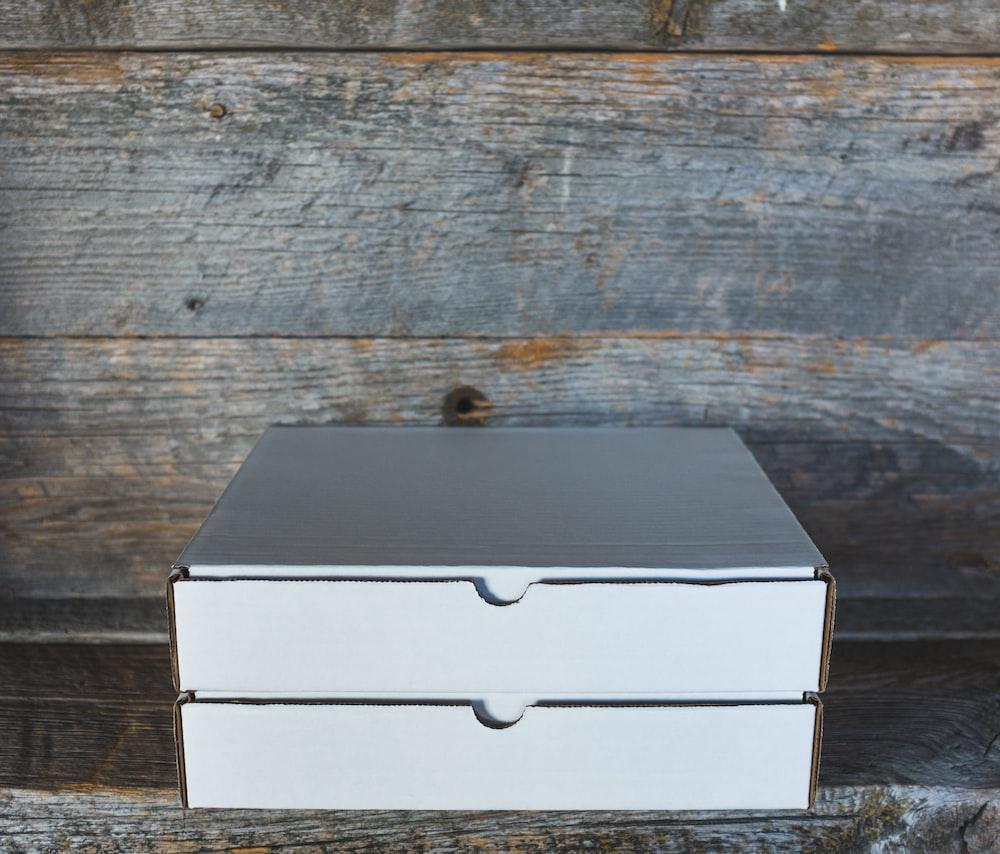 two white cardboard box on wooden shelf