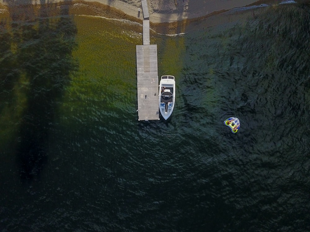 aerial photography of motorboat beside dock