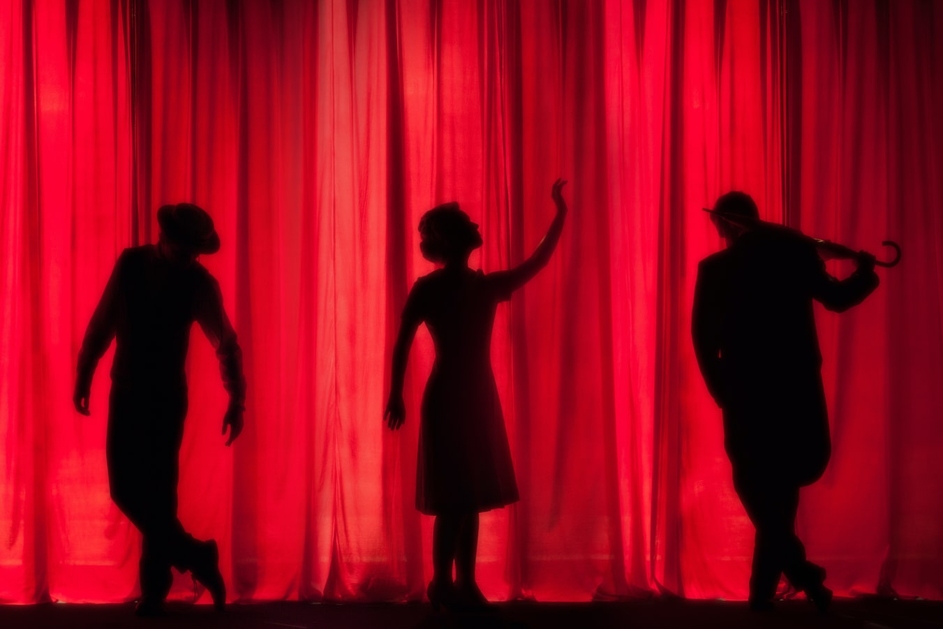 Three backlight Actors in front of a red curtain, performing a play by Canadian Playwrights