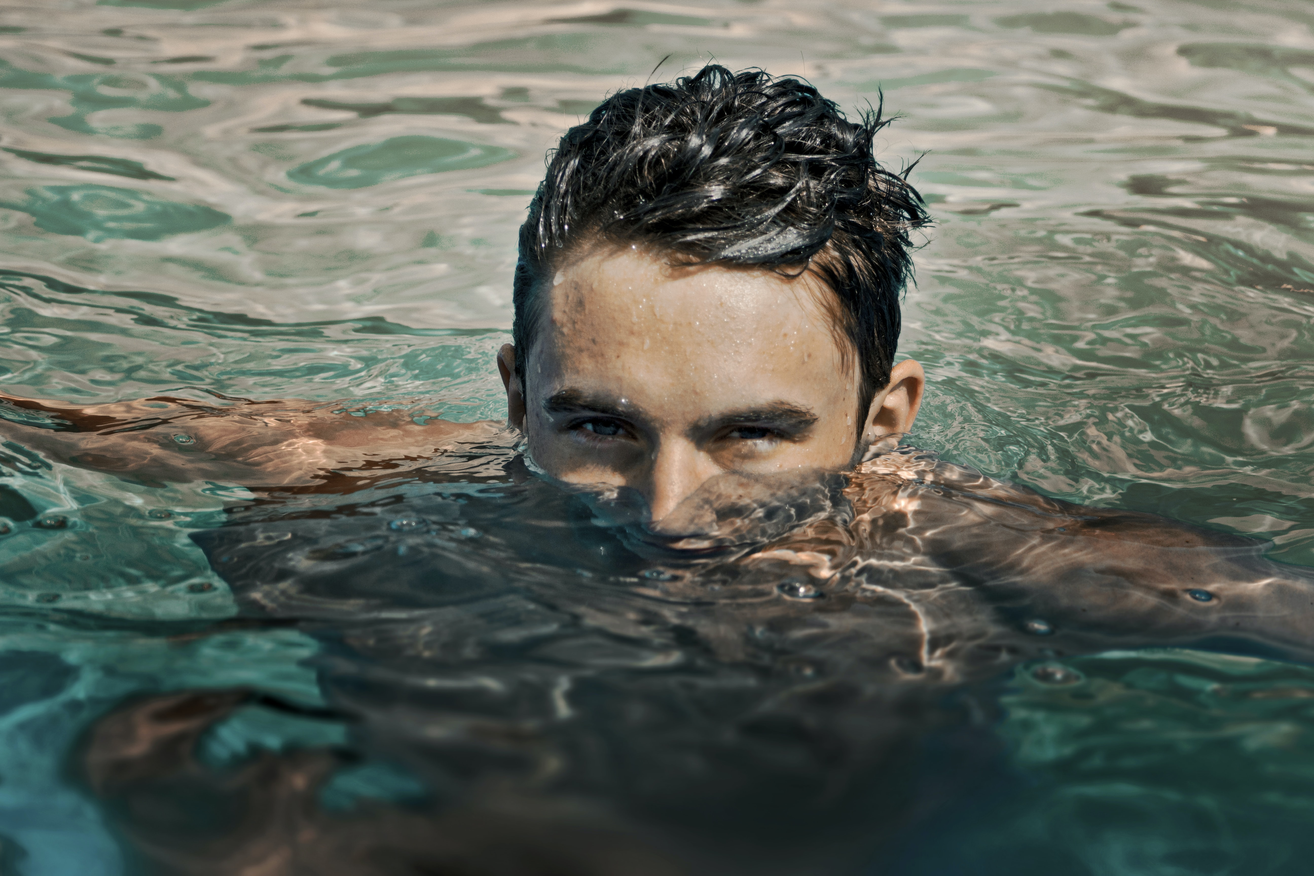 A man with wet hair and a partially submerged face in the water in Grand Rapids
