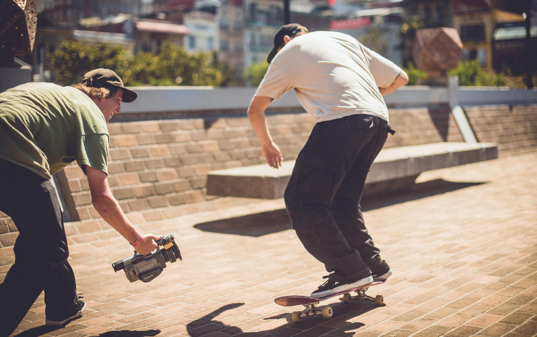 man talking video of person doing skateboard trick