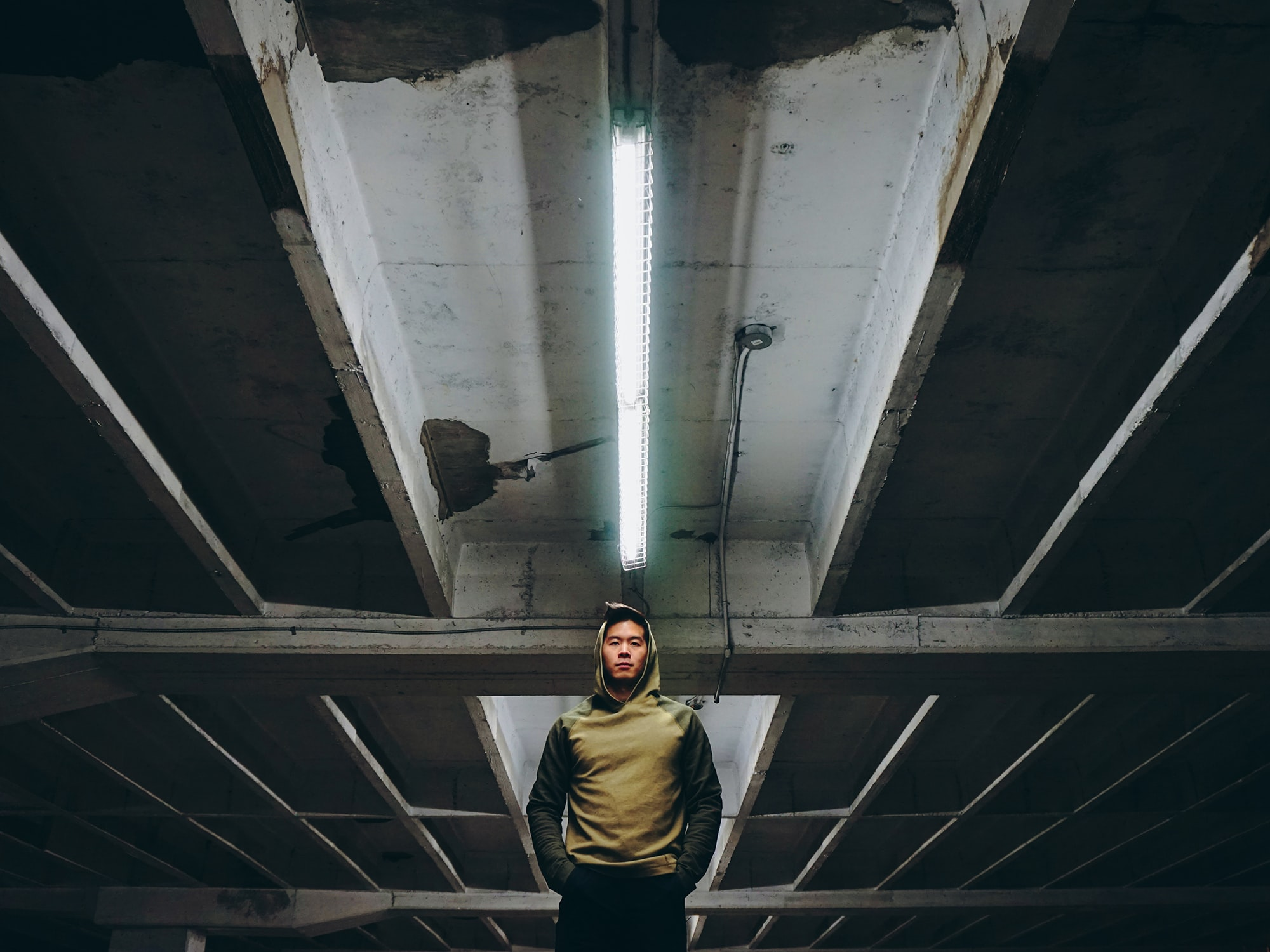 low-angle photography of man wearing hooding standing on underground parking lot