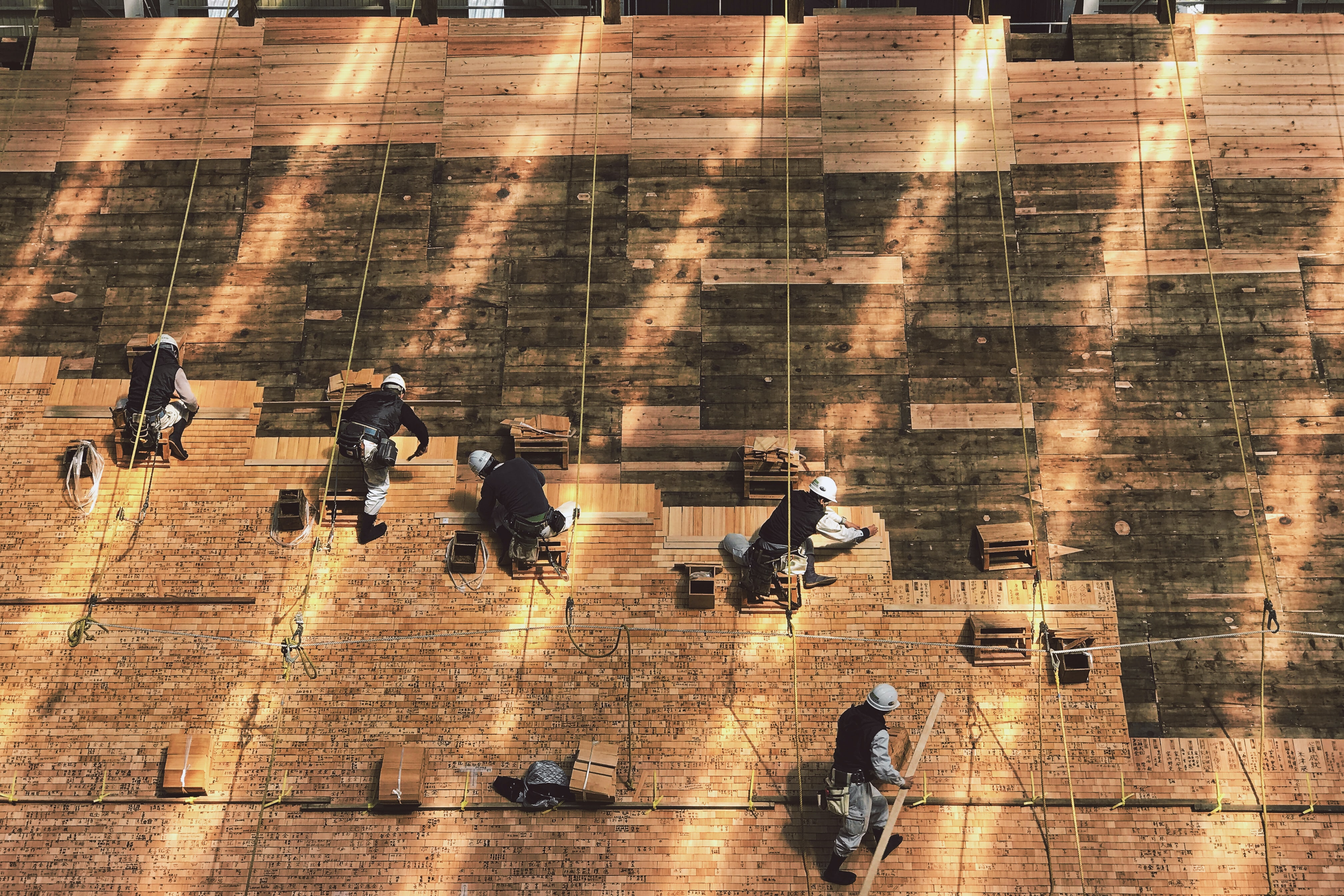 Construction workers laying out tiles on a roof