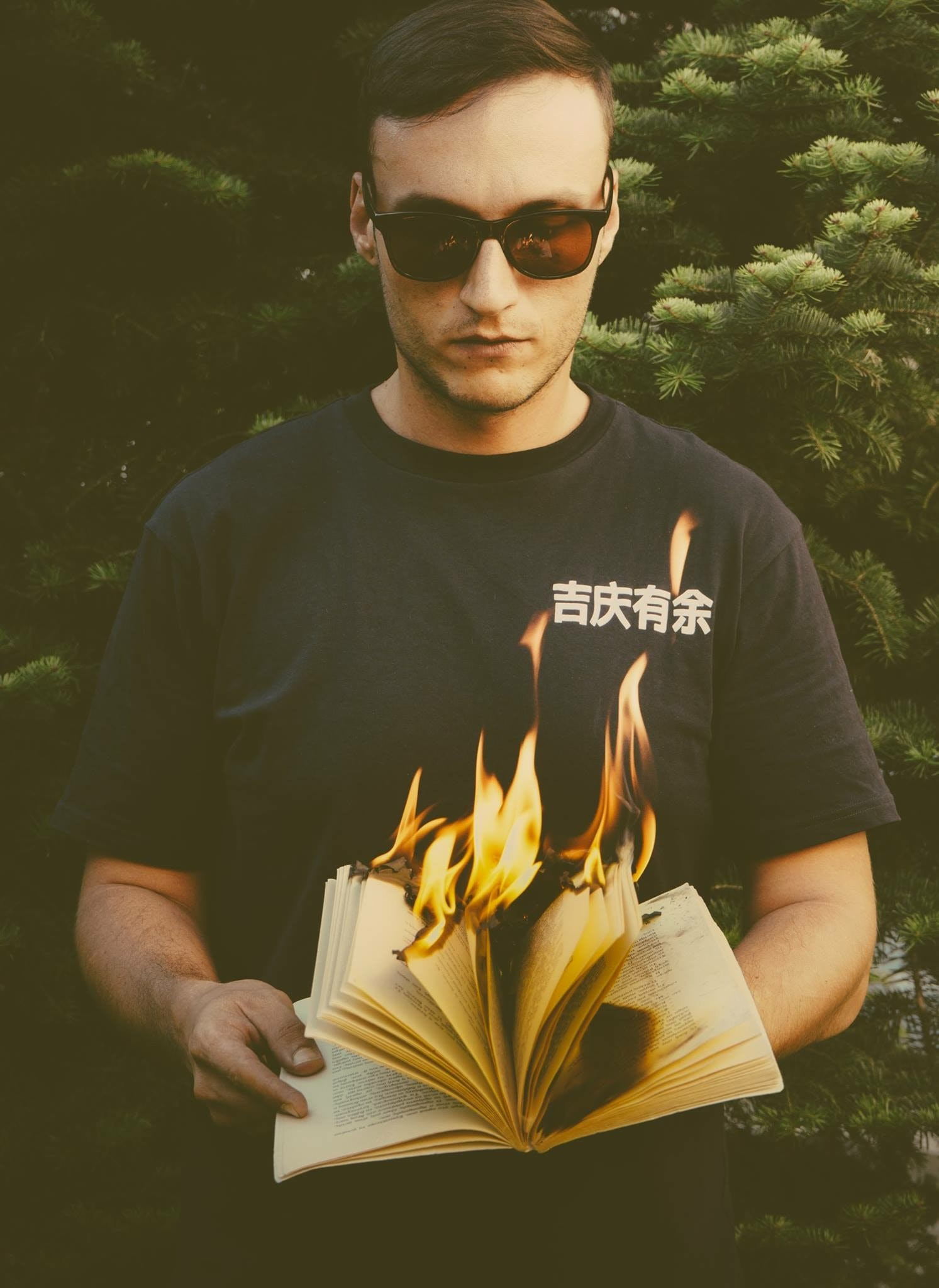 man standing while holding burning book