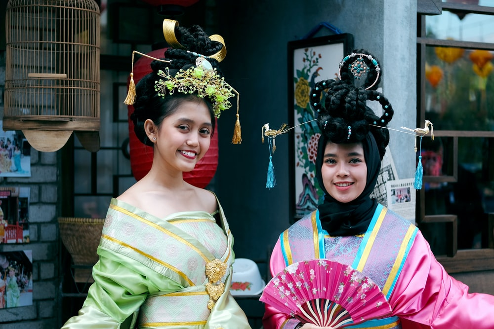 women wearing green and pink traditional dresses
