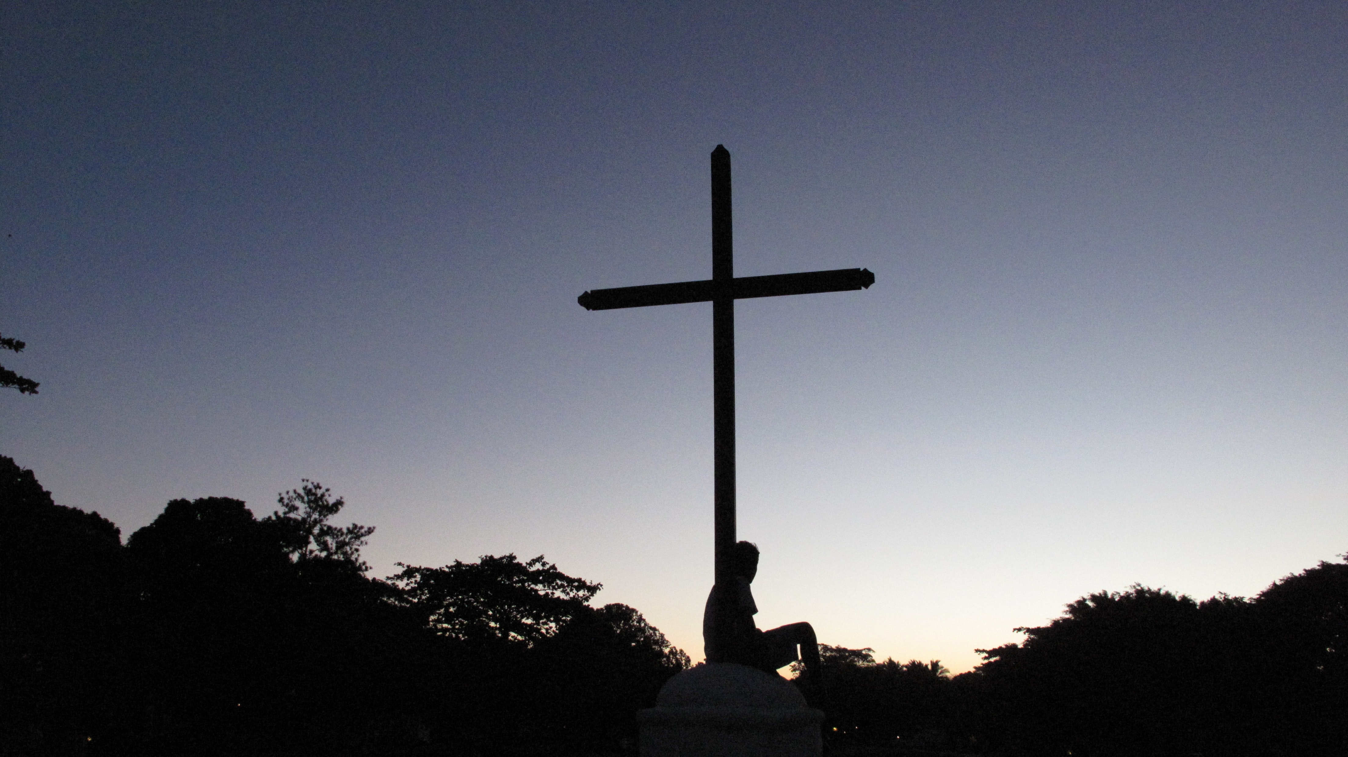 silhouette of person sitting below cross