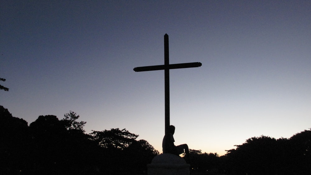 silhouette of person sitting below cross