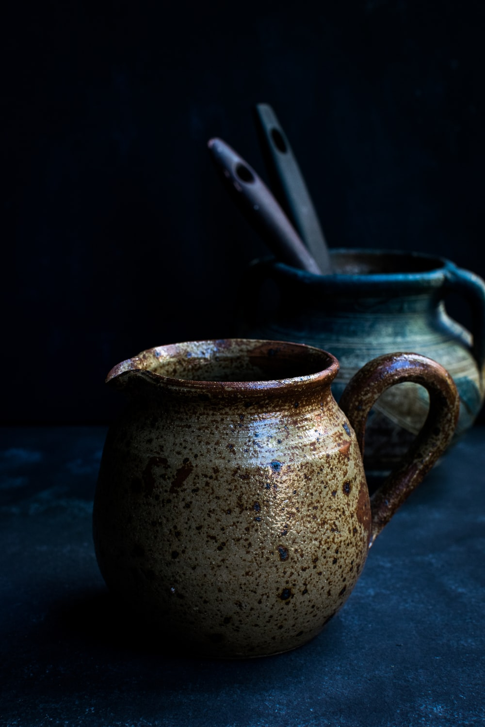 shallow focus photo of brown ceramic pitcher
