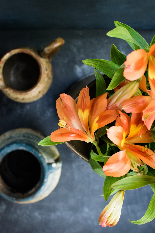 orange blooming flowers on white ceramic vase