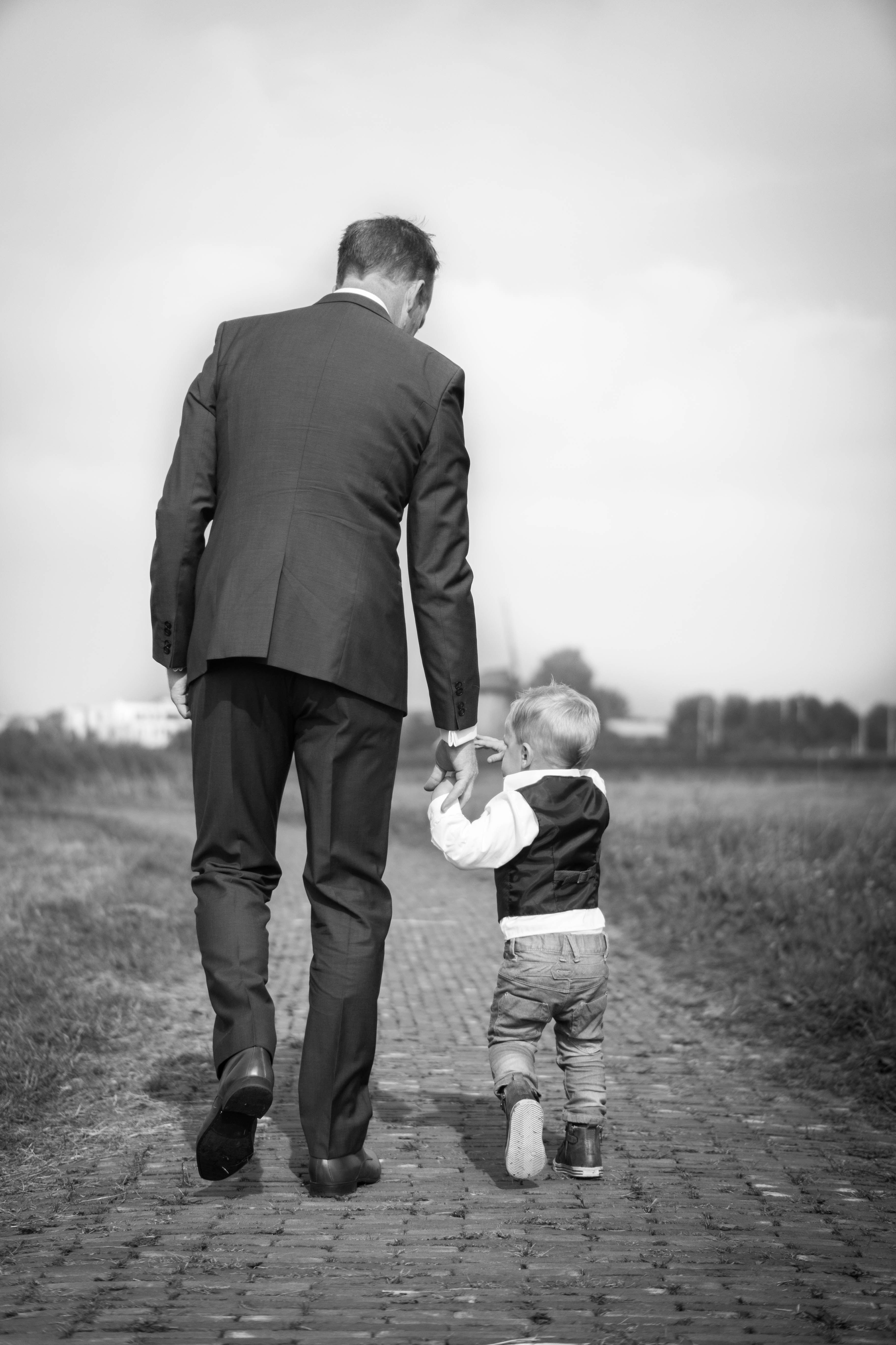 Father and his young son dressed up walking hand in hand