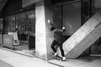 grayscale photo of man doing skateboard tricks