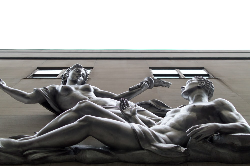 statue of nude woman and man on building