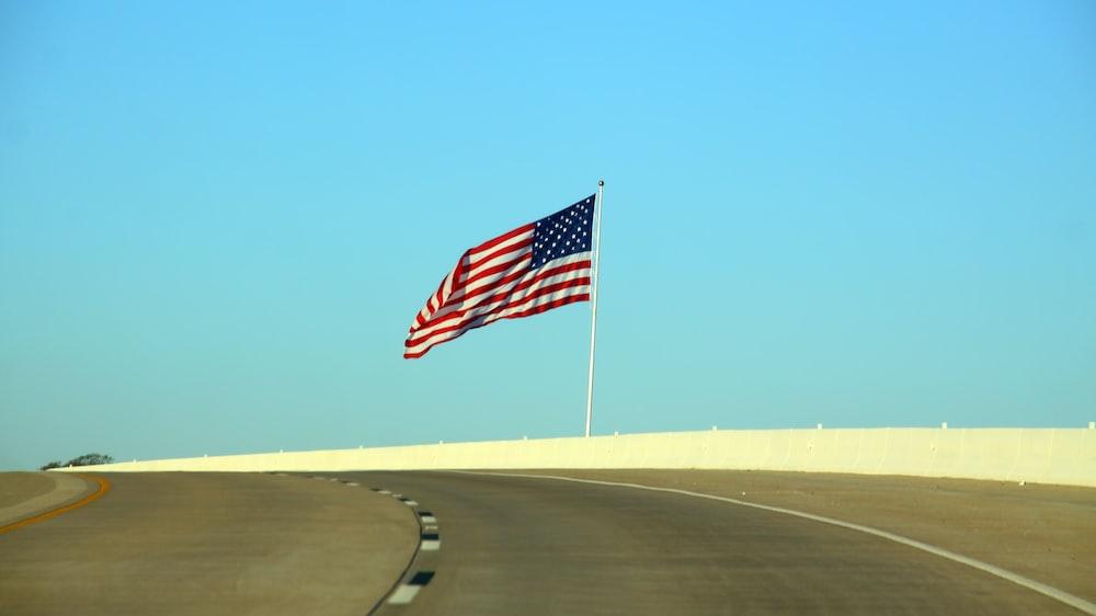 US flag beside road at daytime