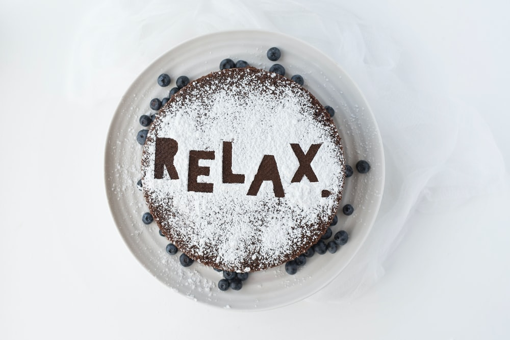 Chocolate and blueberry cake with powdered sugar that says Relax