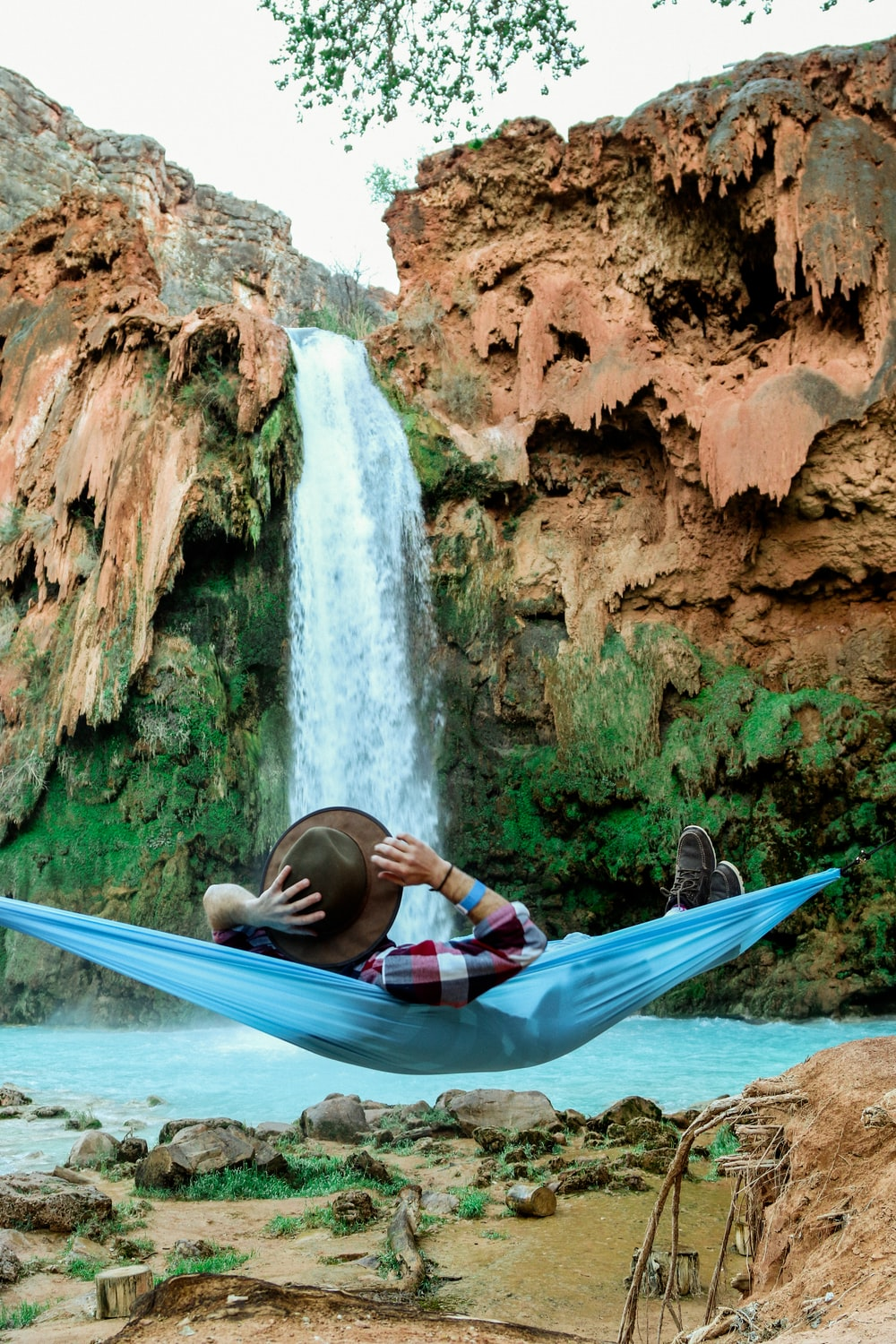 man laying on blue hammock in front of waterfalls