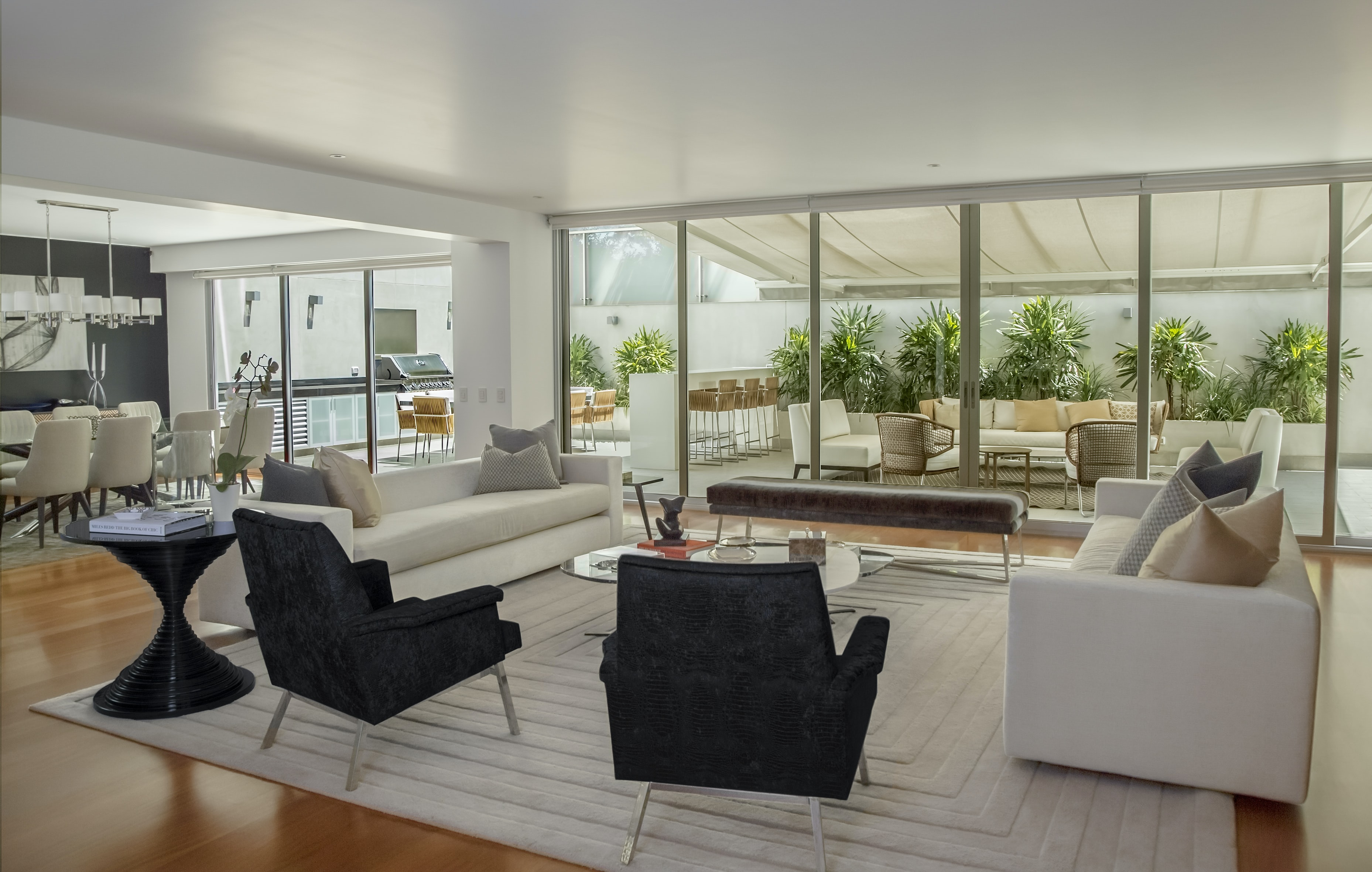 Living and dining room with black and white furniture facing patio with plants and furniture