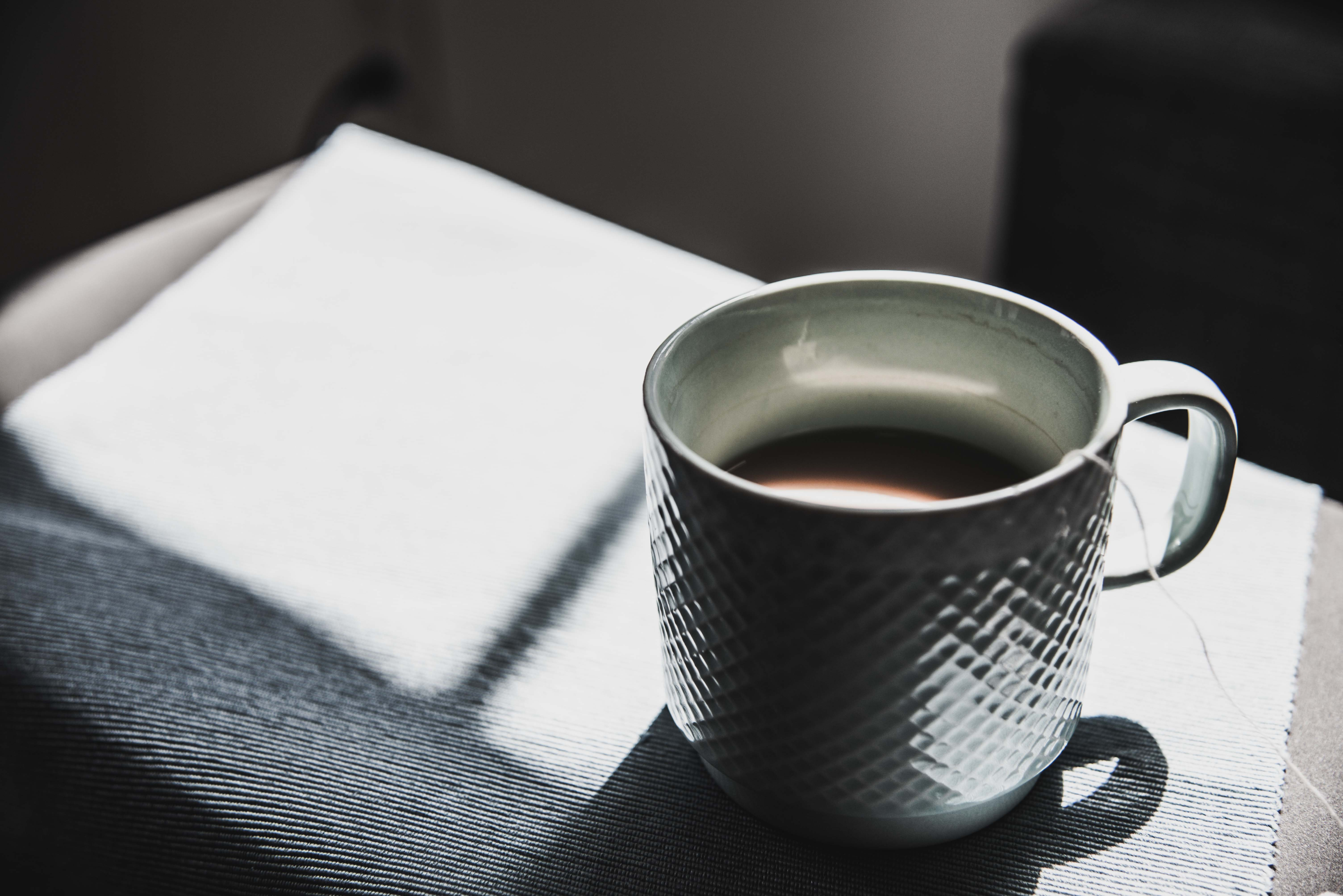 A cup of tea in a white ceramic mug on a tablecloth in the sun with a shadow