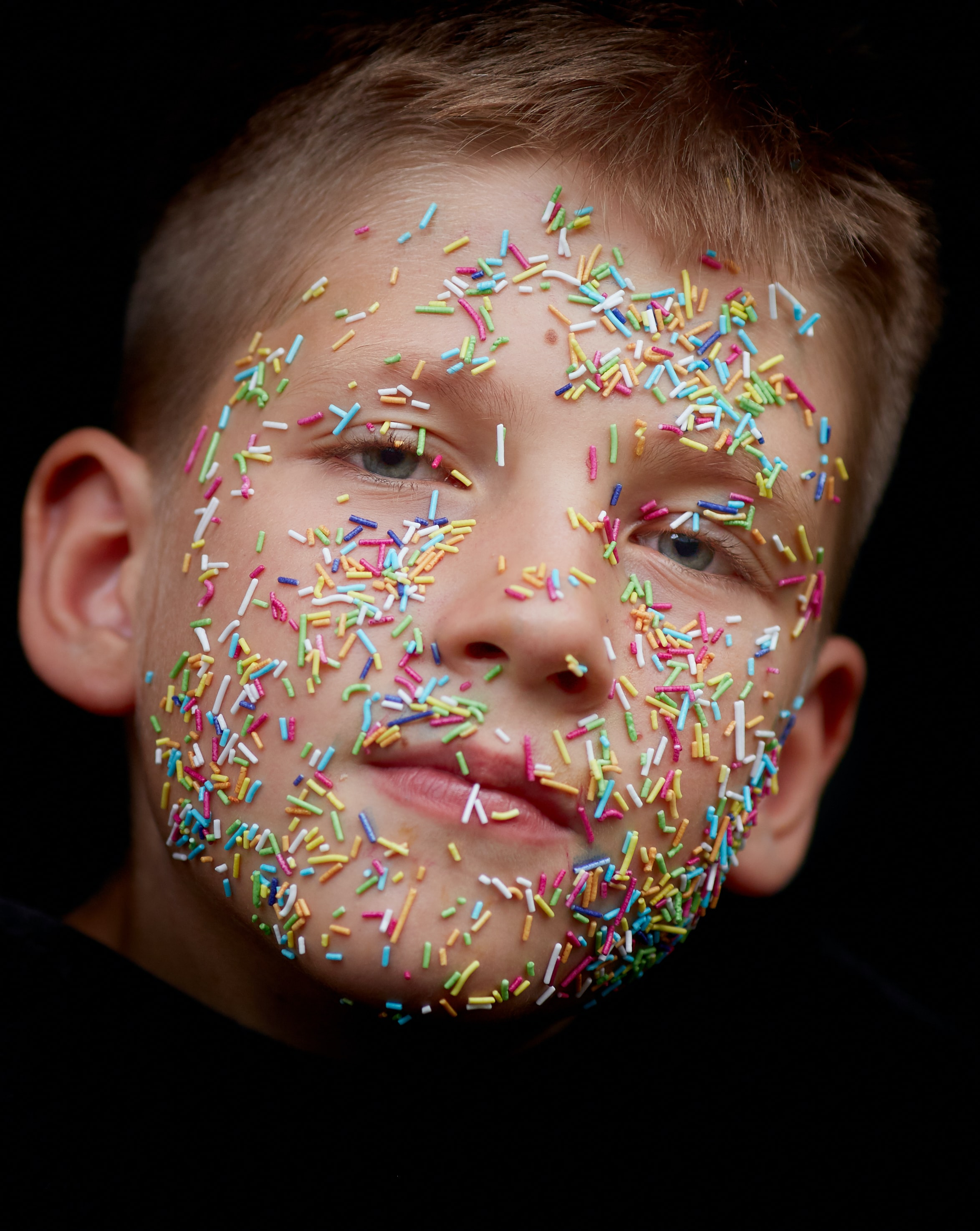 assorted-color sprinkler candies on boy's face
