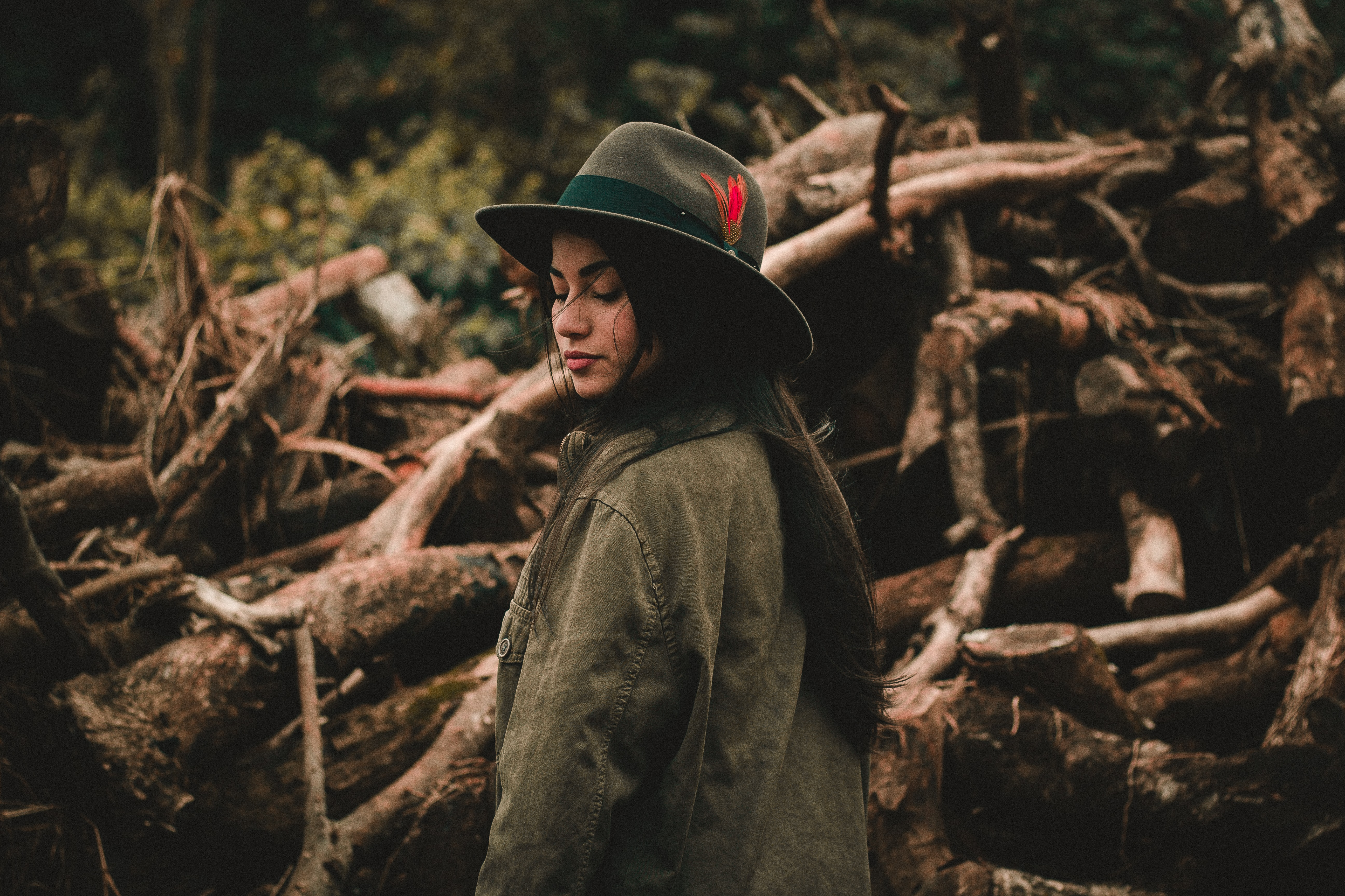 A woman in an olive green jacket and feathered hat stands in front of fallen trees