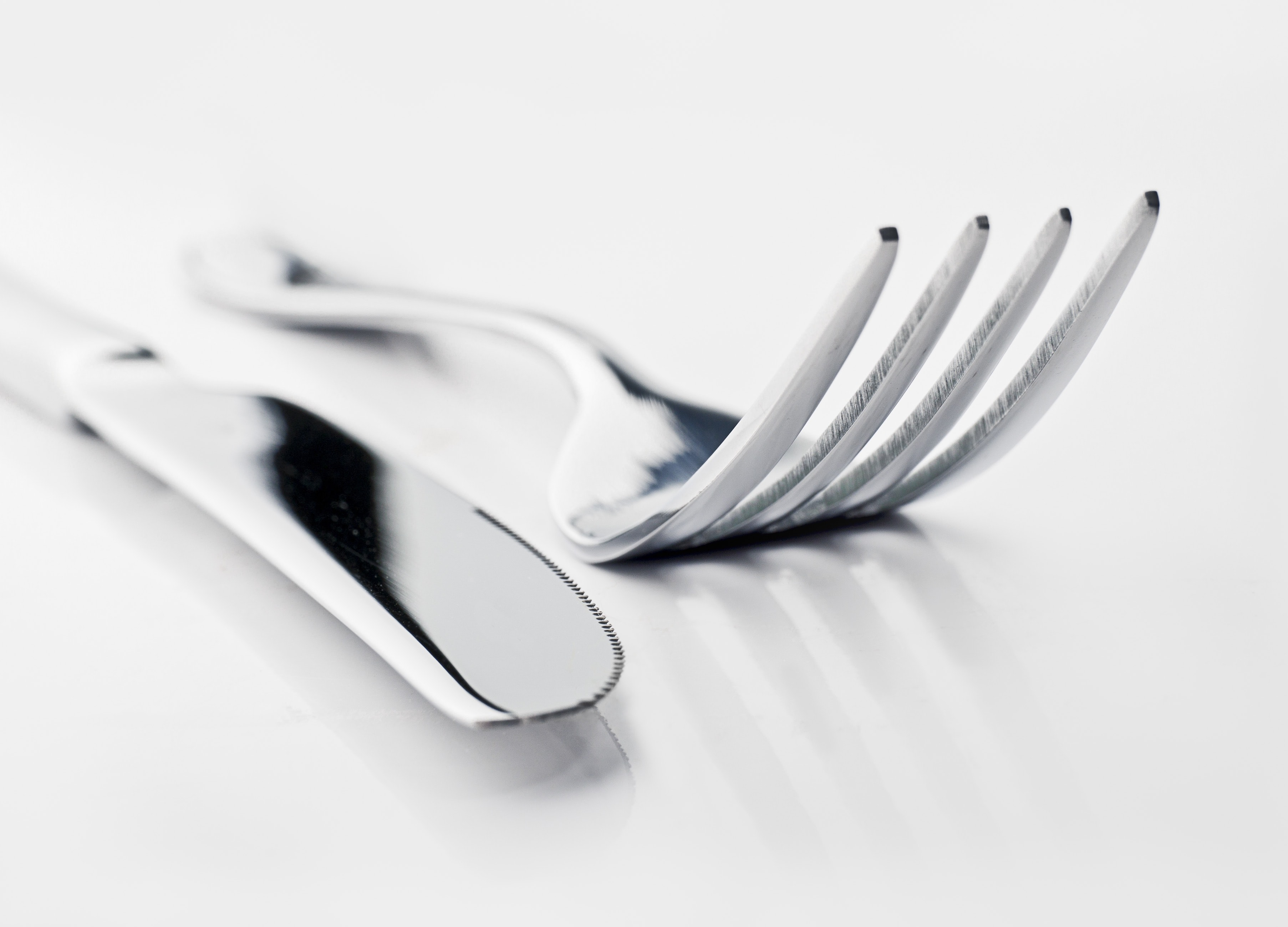 Shiny fork and knife on a white reflective table