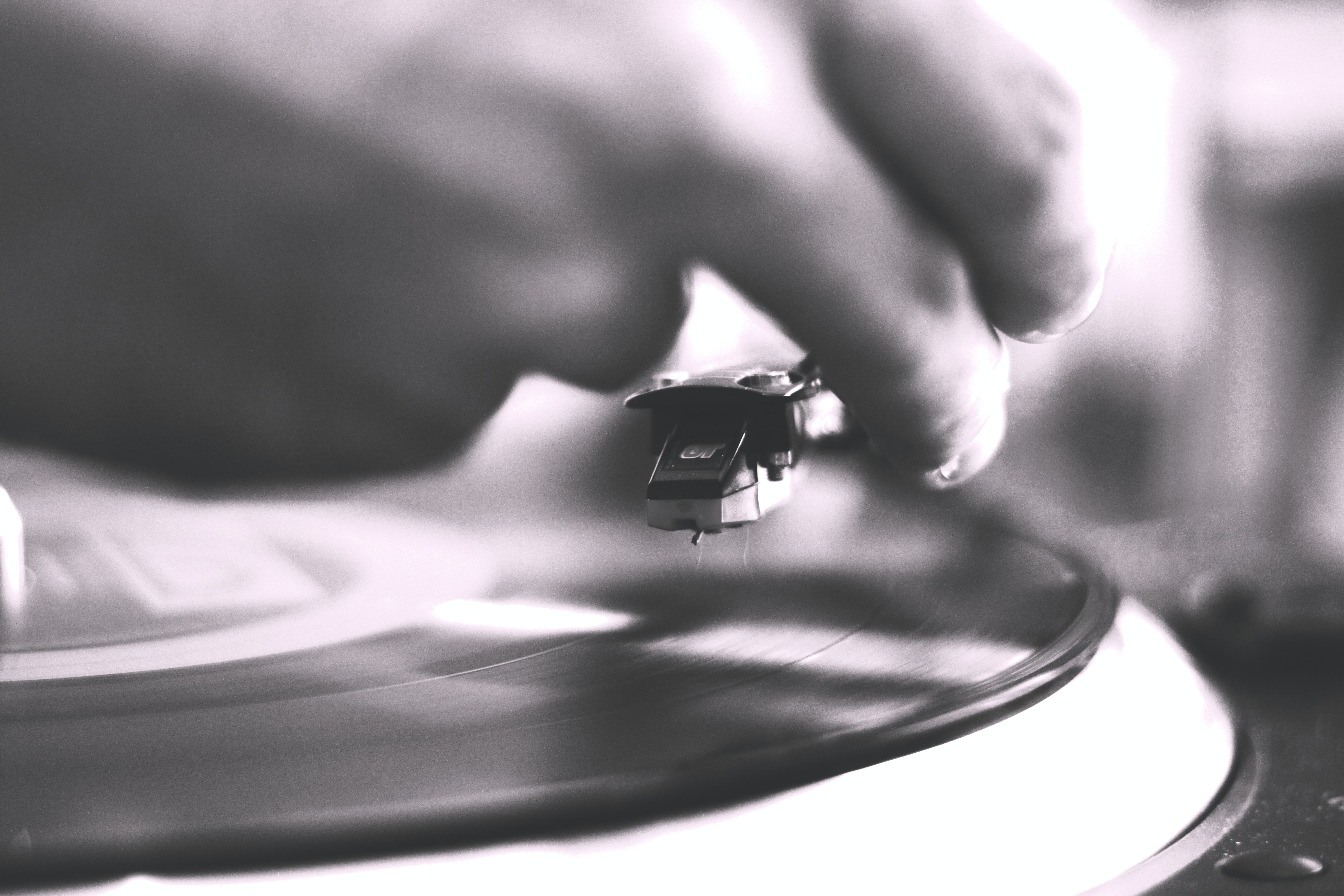 Unfocused black and white shot of hand putting needle on a record on a turntable