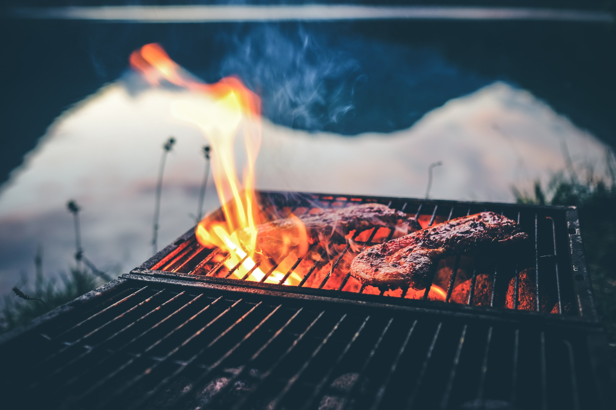 steak on charcoal grill with fire
