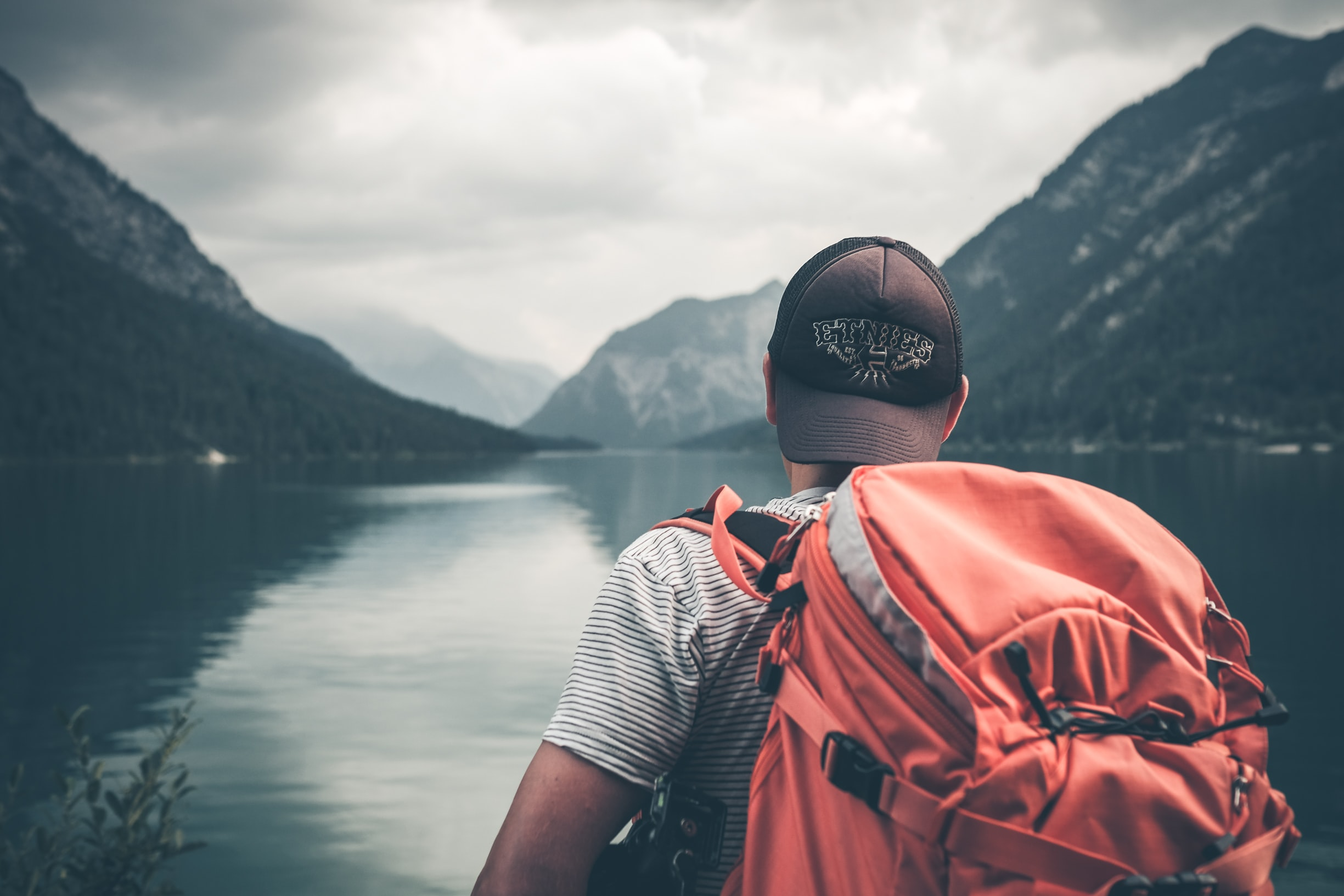 Hiker with a heavy backpack looking out at mountains and still water