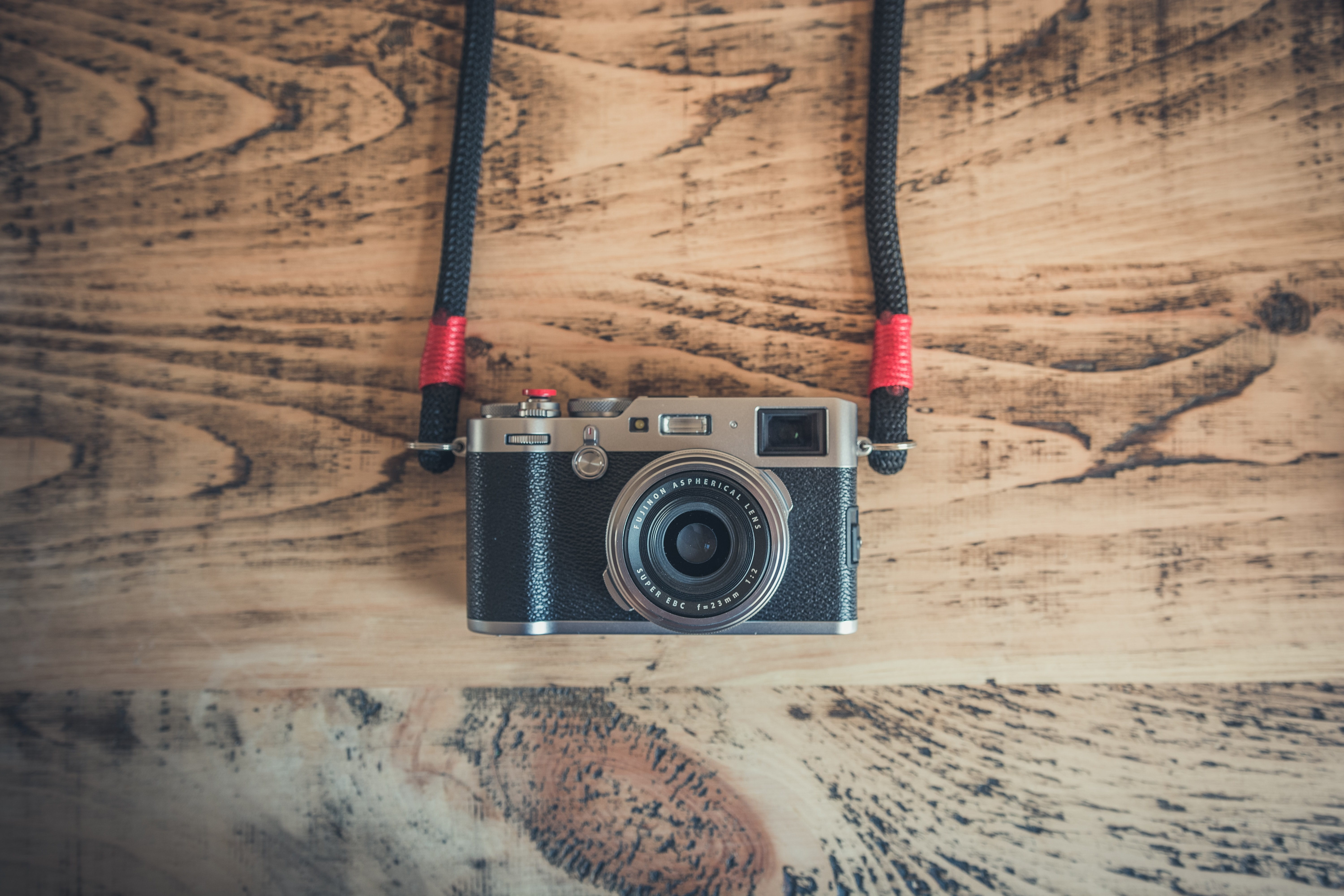 Black camera on straps laying on a wooden surface