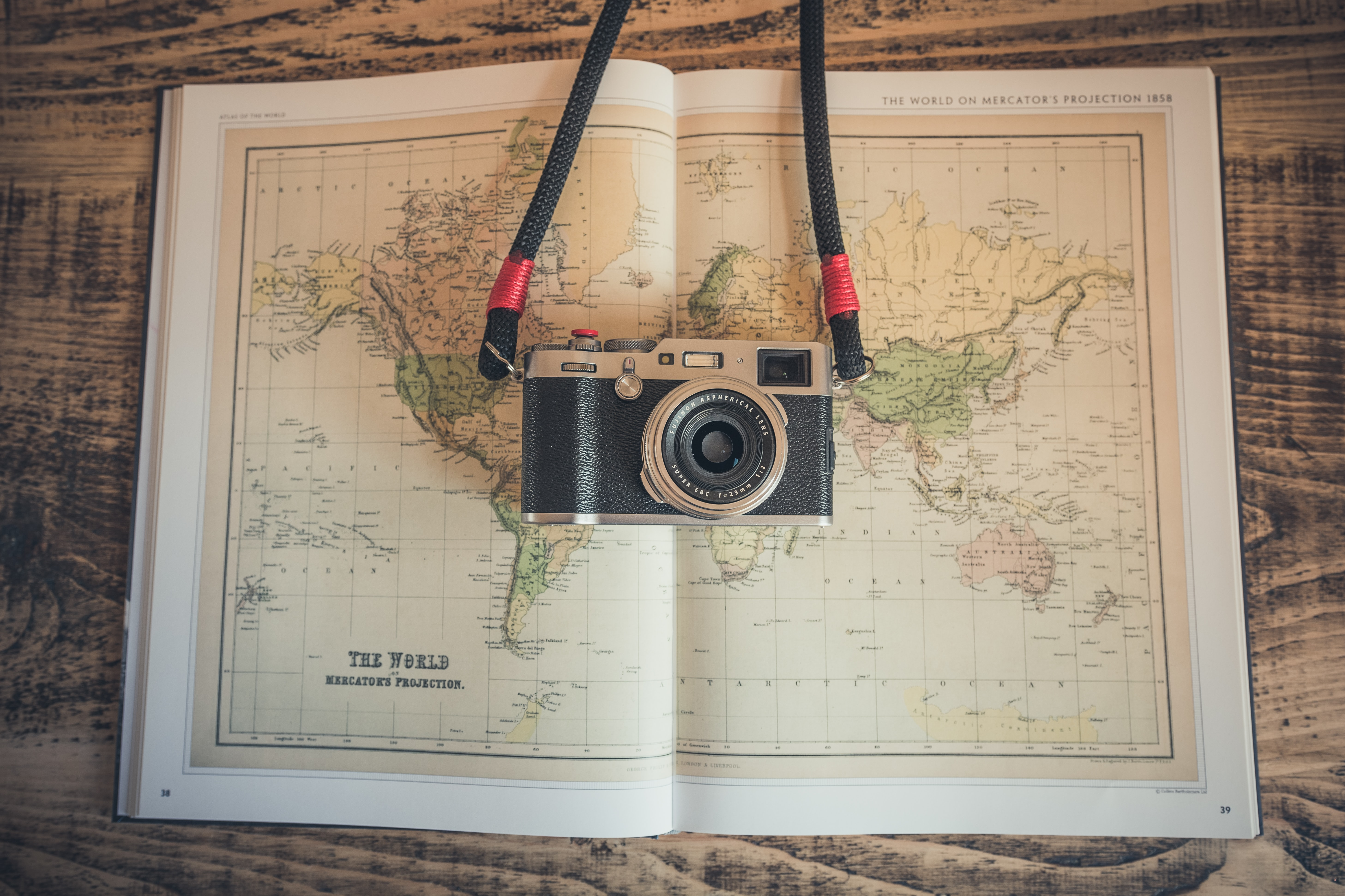 the vintage camera over a book spread of the world map