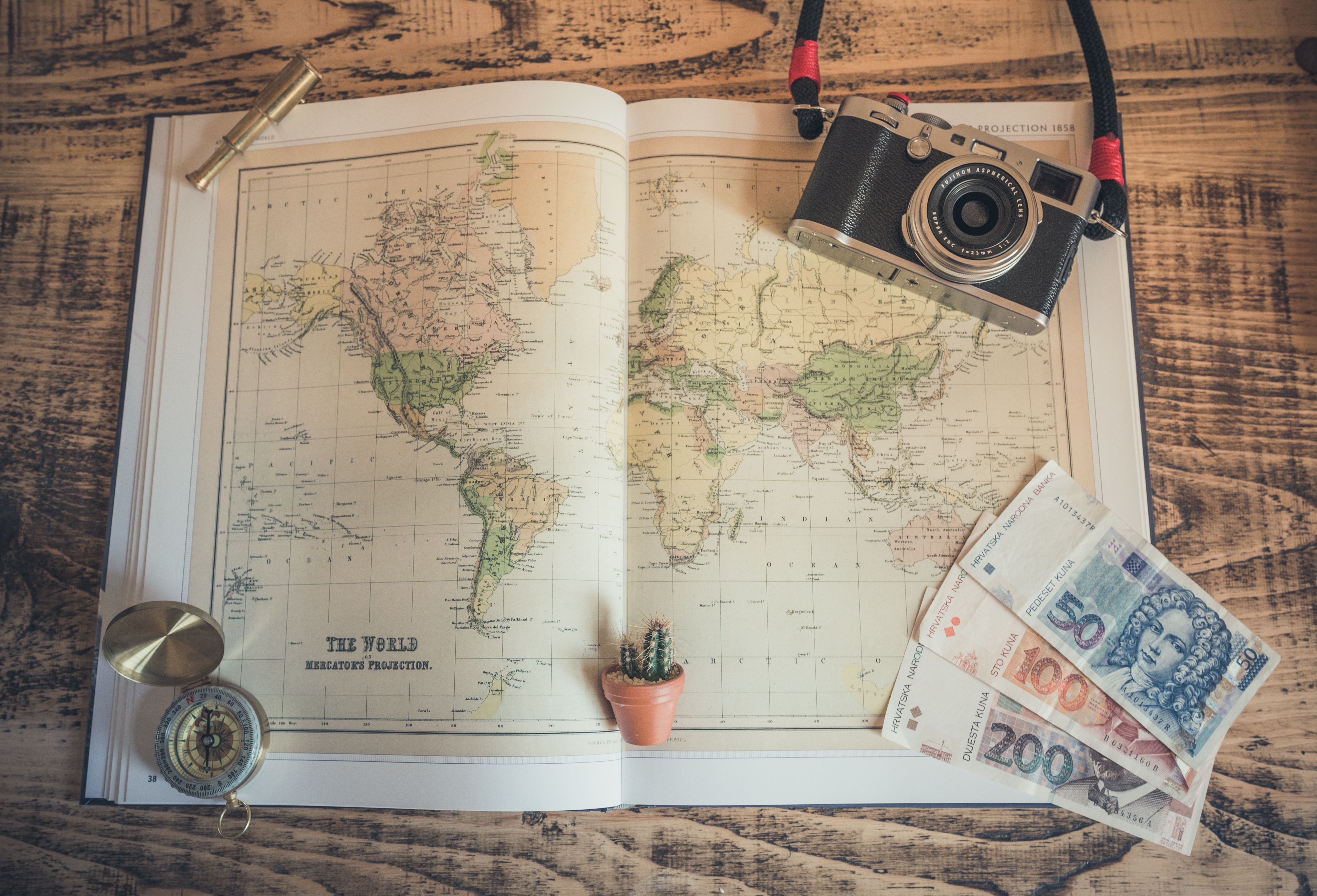 Flat lay photography of a world map, money, compass, cactus and a tiny telescope model.