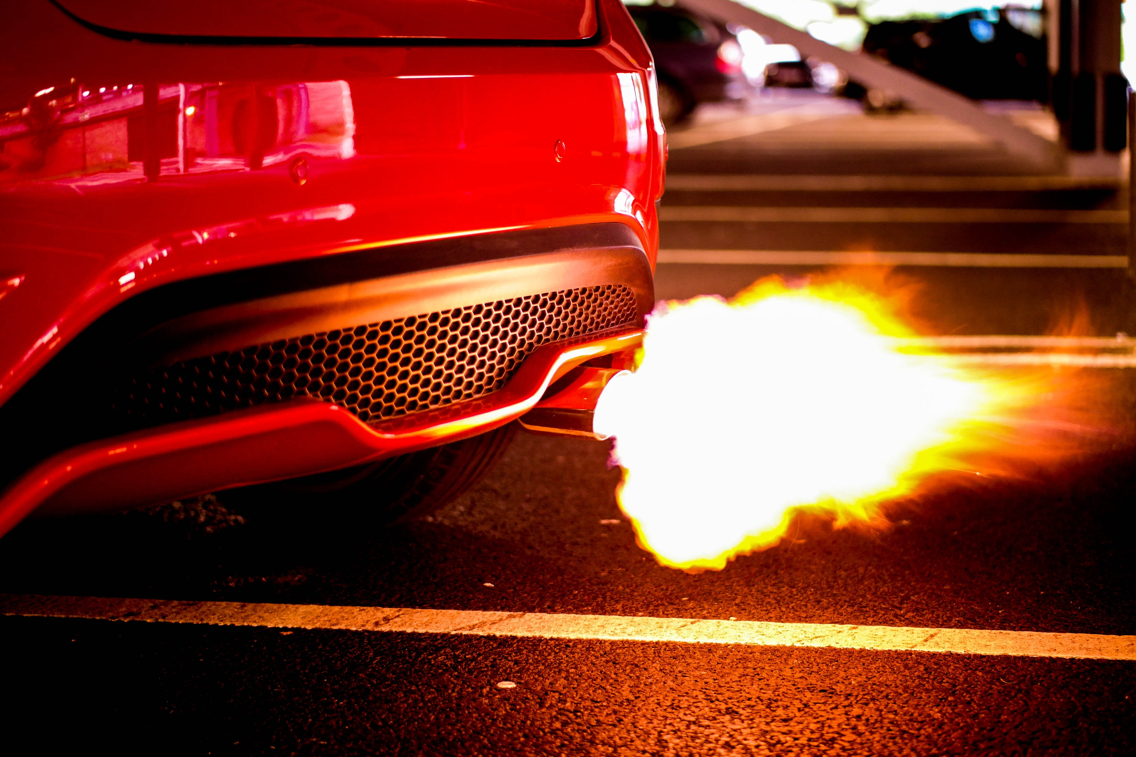 A red sports car sputtering a flame in its exhaust in a night time setting beside a parking lot