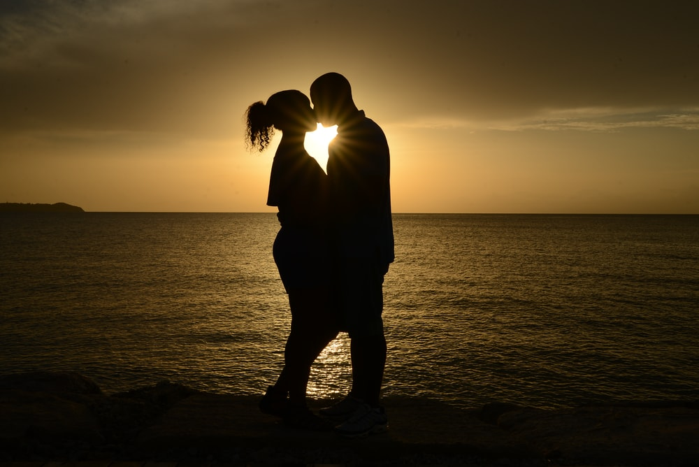 silhouette couple kissing against the sun