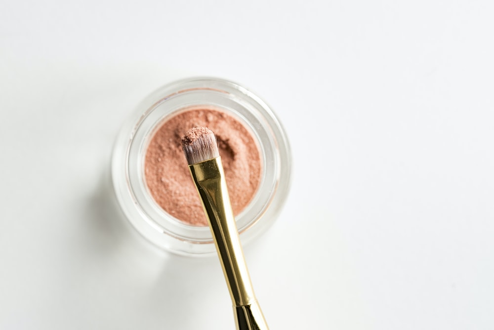 brown makeup brush in front pink powder on glass case