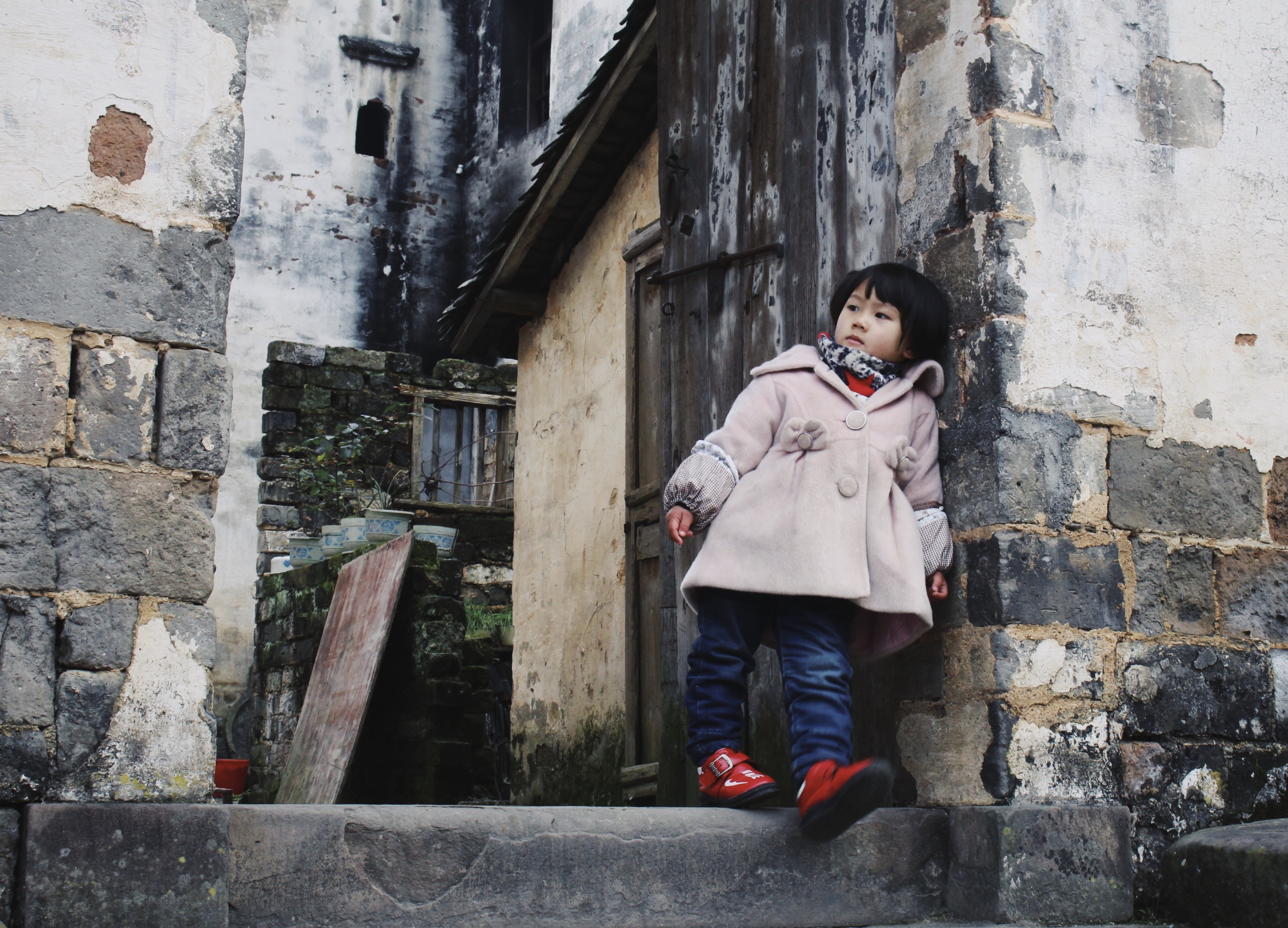 girl leaning on concrete wall