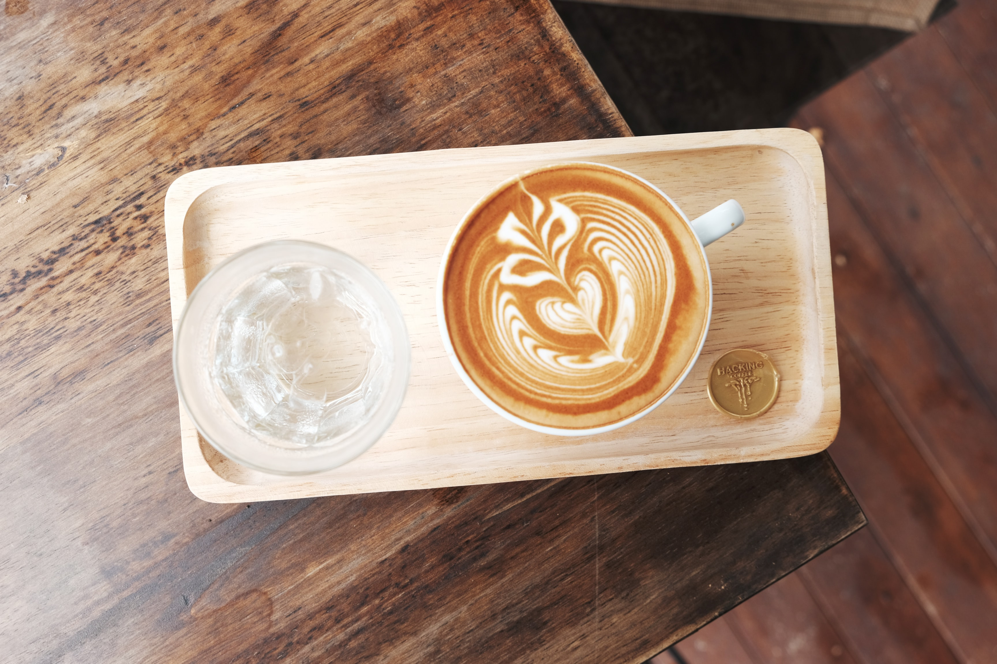 Cappuccino in a white mug with foam art on a wooden tray next to a clear empty glass