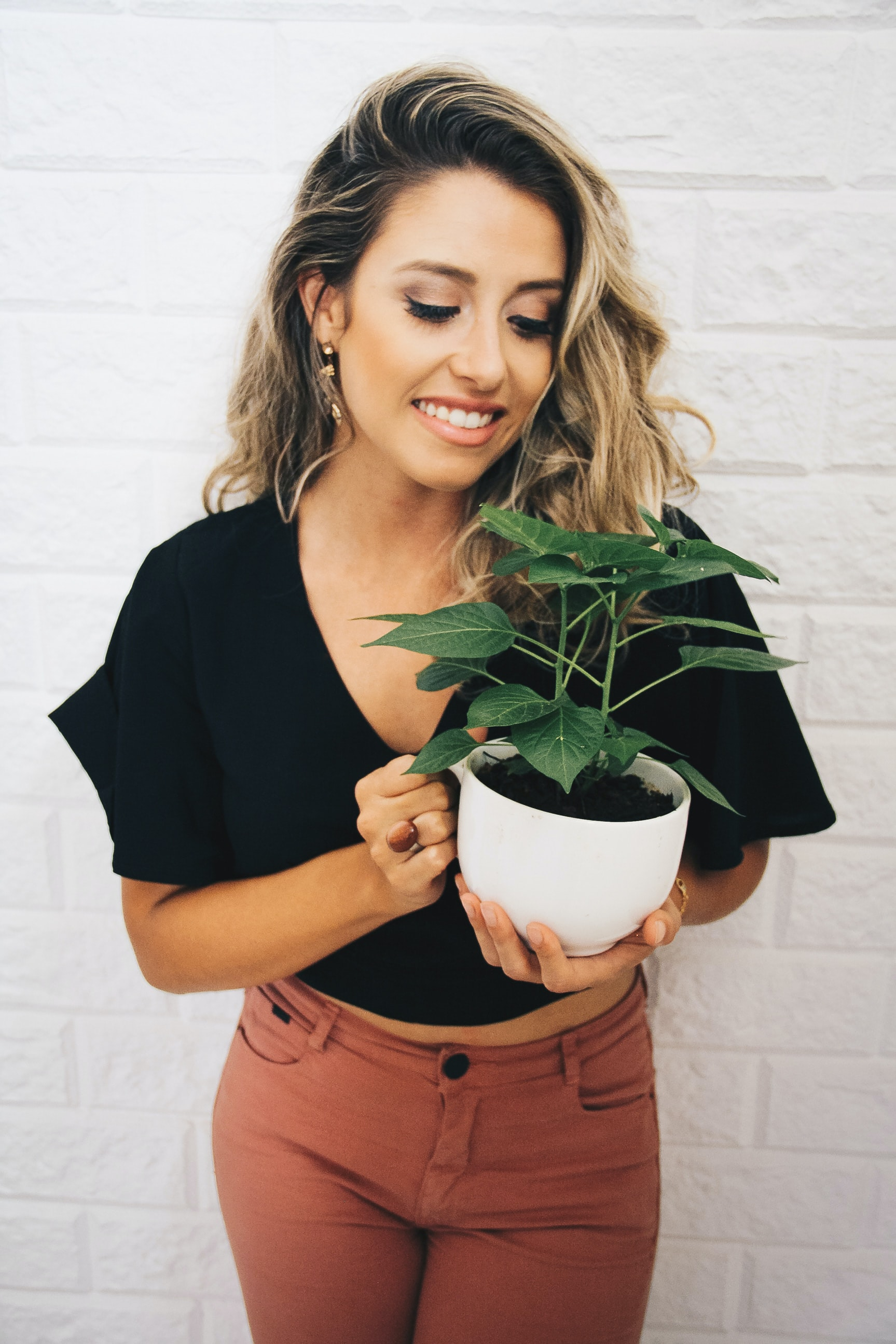 woman smiling while holding potted plant