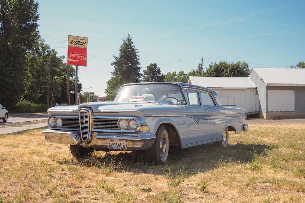 classic teal sedan near house during daytime