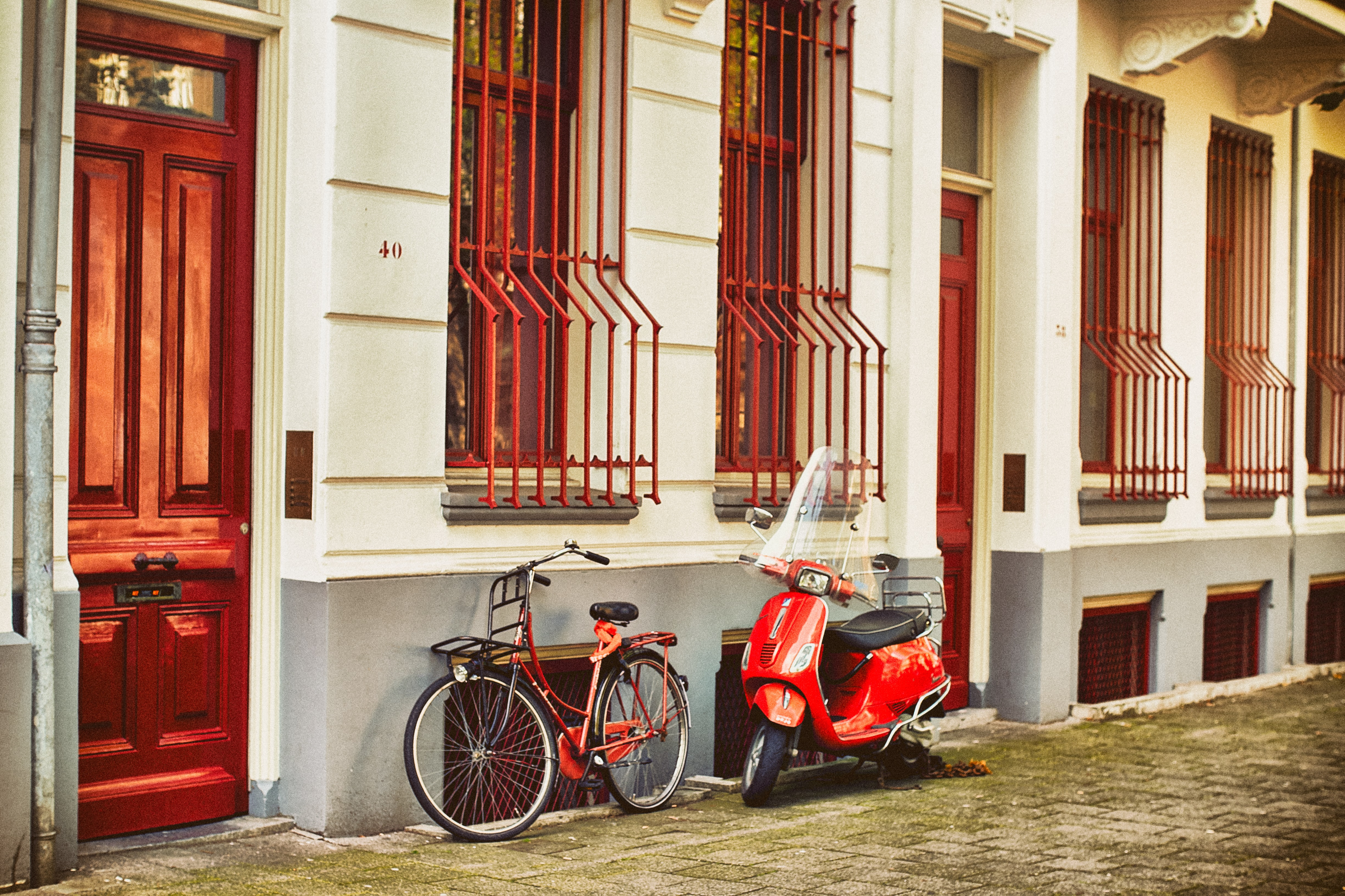 red motor scooter parked beside house