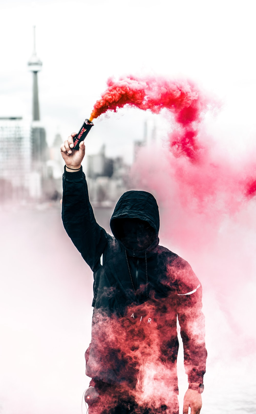 A person in a black hoodie with obscured face holds up a pink smoke grenade