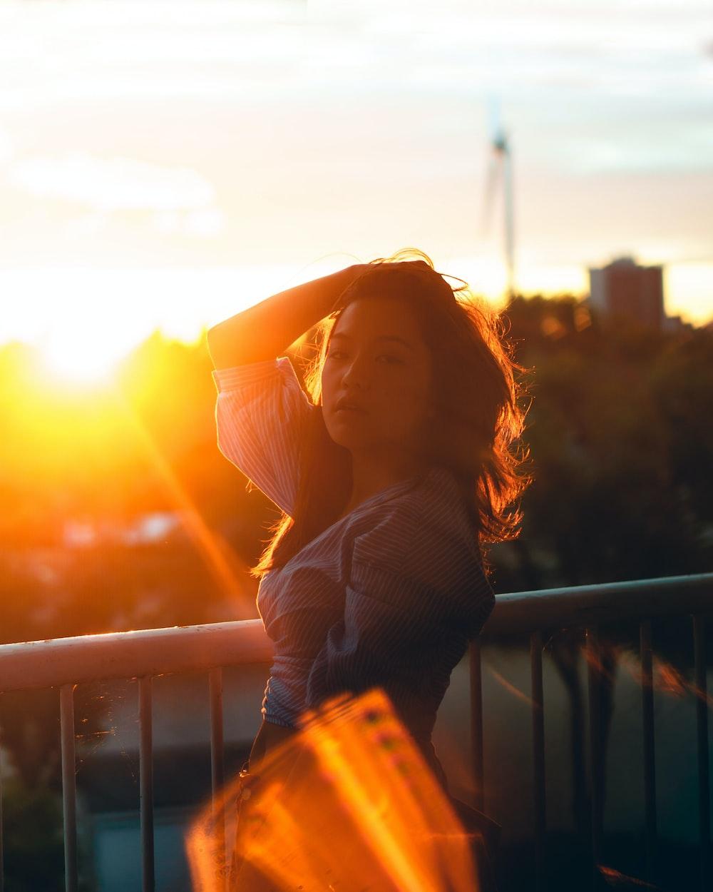 woman posing near handrail during sunset