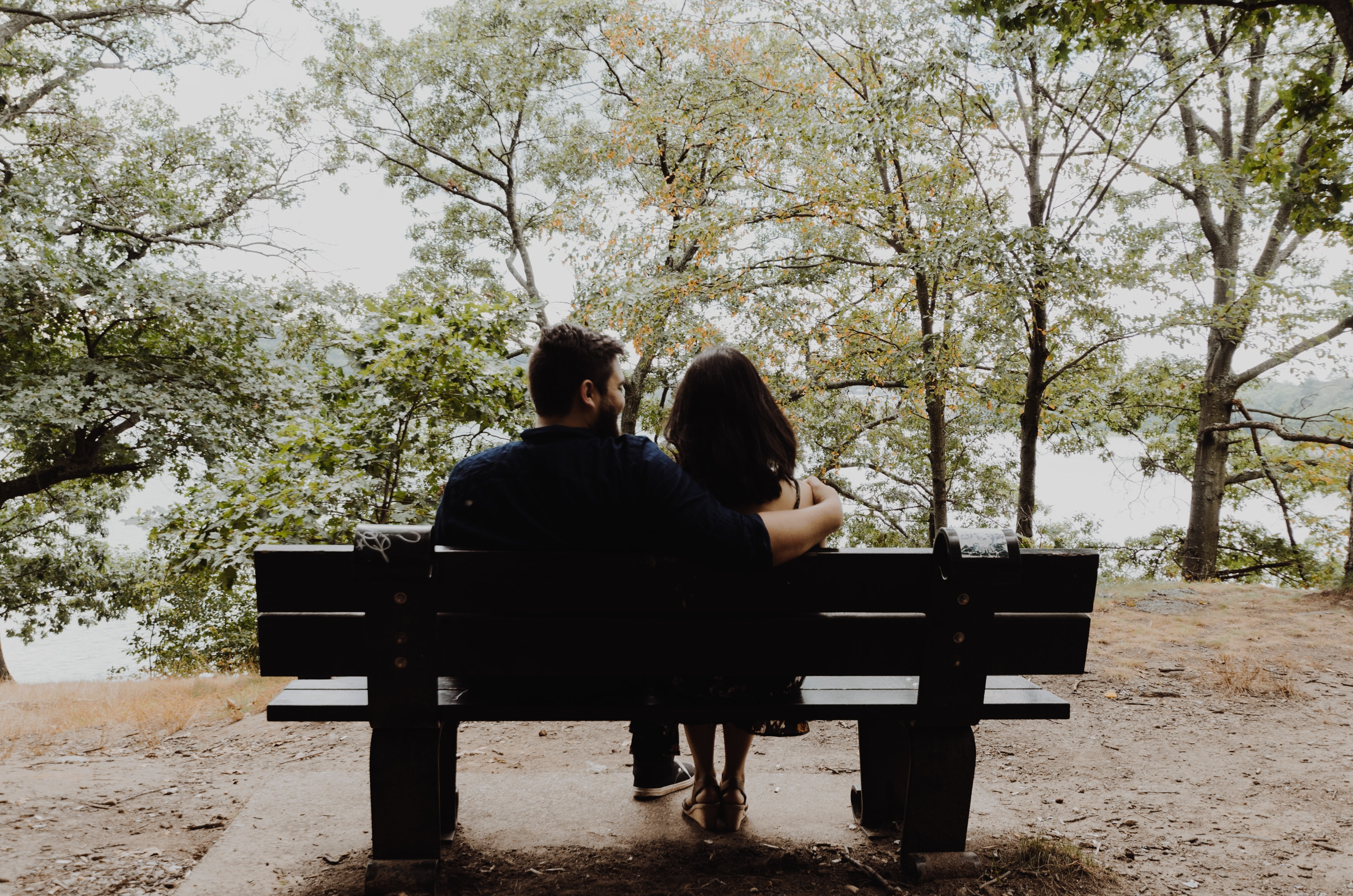 man looking to woman sitting on black wooden bench in front of tall trees during daytime
