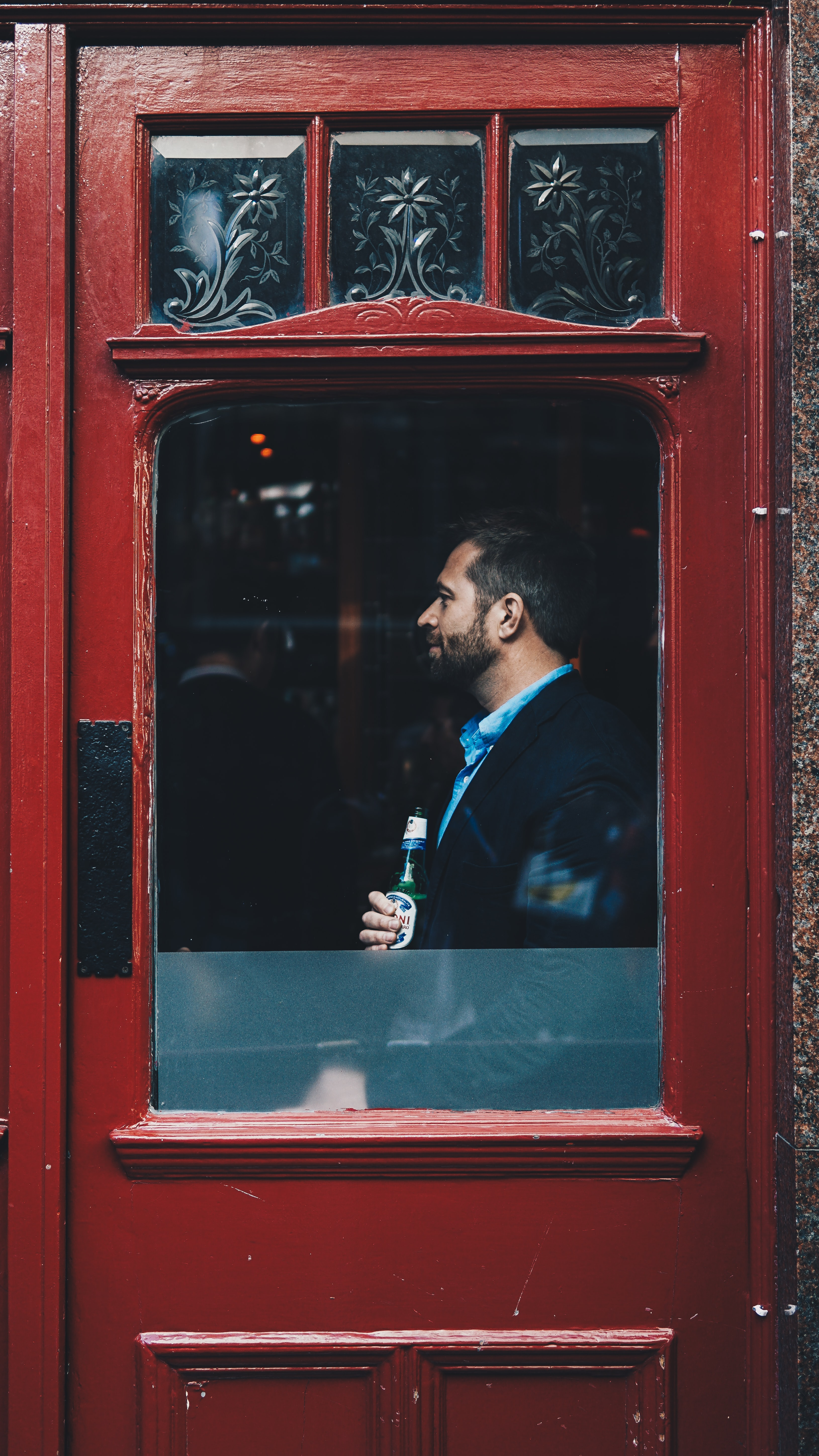 A man holding a beer and standing at the window of a red door in China Town