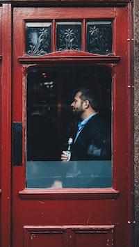 man standing beside red wooden glass door inside the building