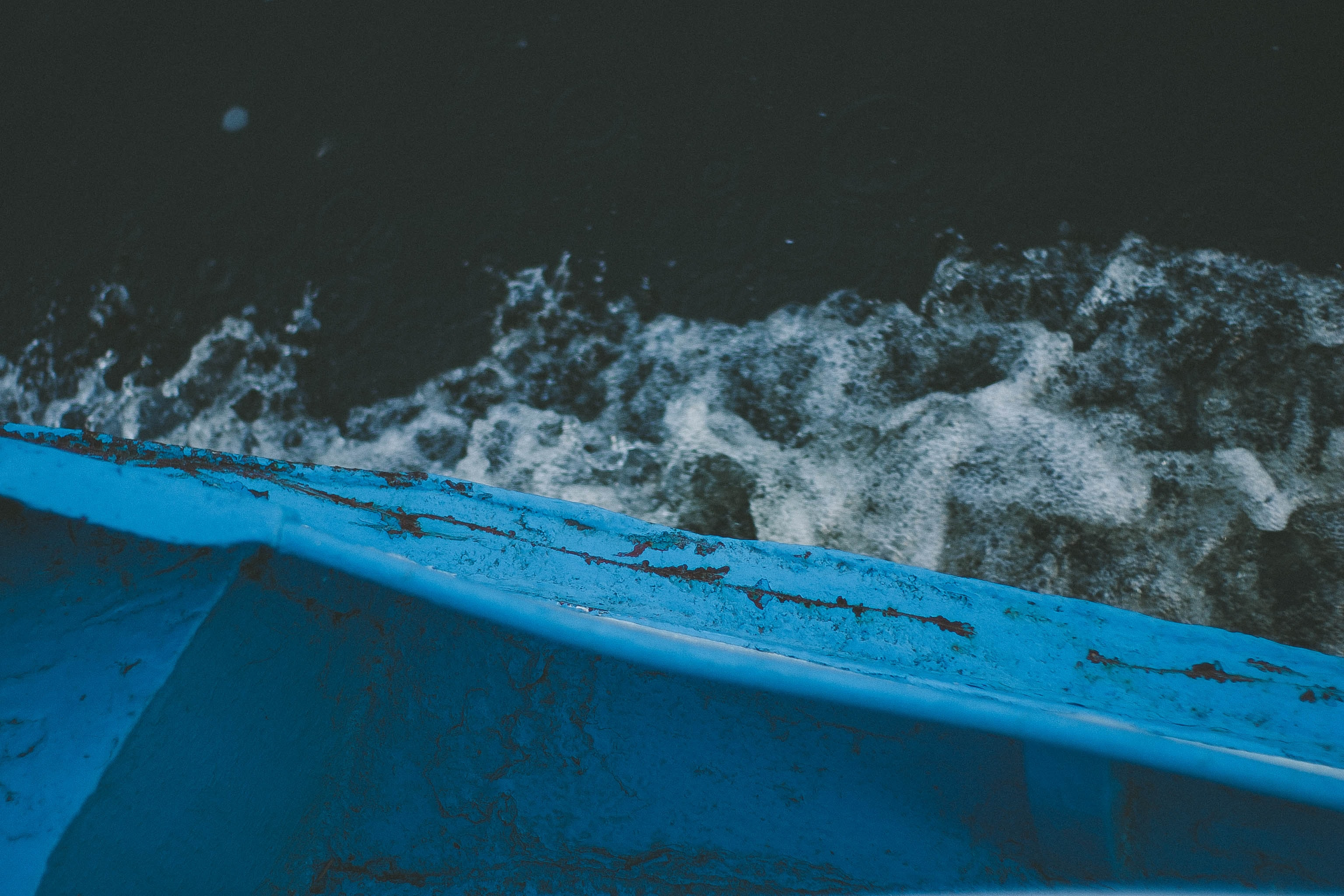 blue boat on body of water