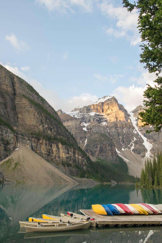 kayak on dock near lake and mountain at daytime
