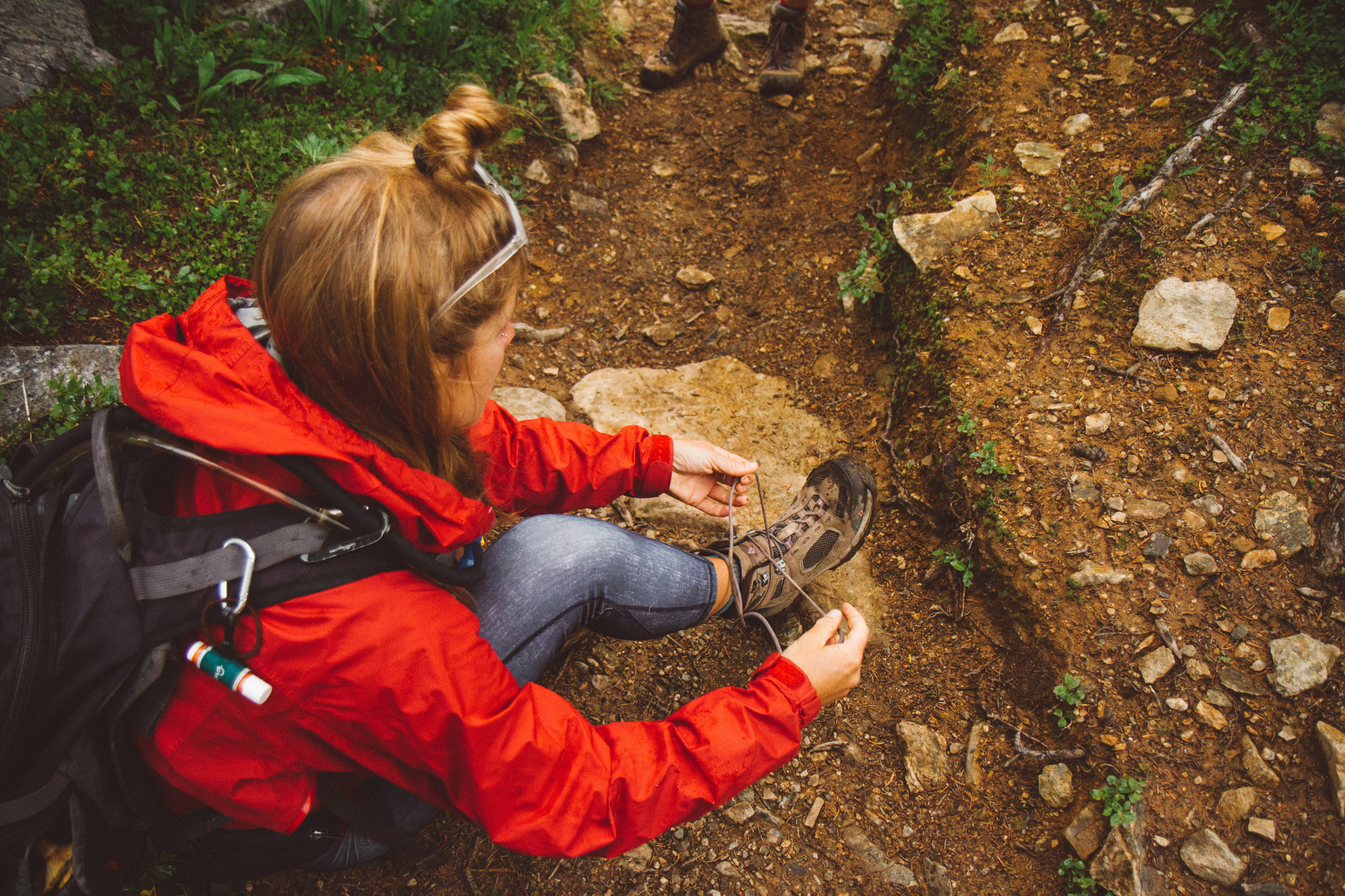 A woman in a backpack and jacket sits on dirt and rocks tying her hiking boots