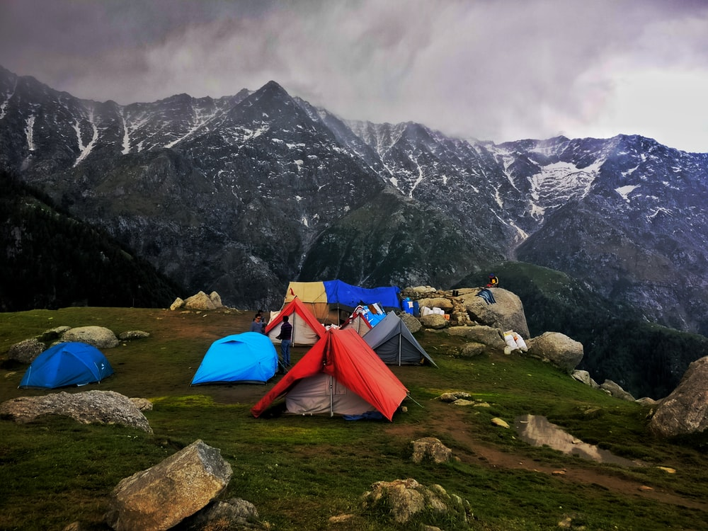 assorted-color outdoor tents on green grass field near gray mountain under gray sky