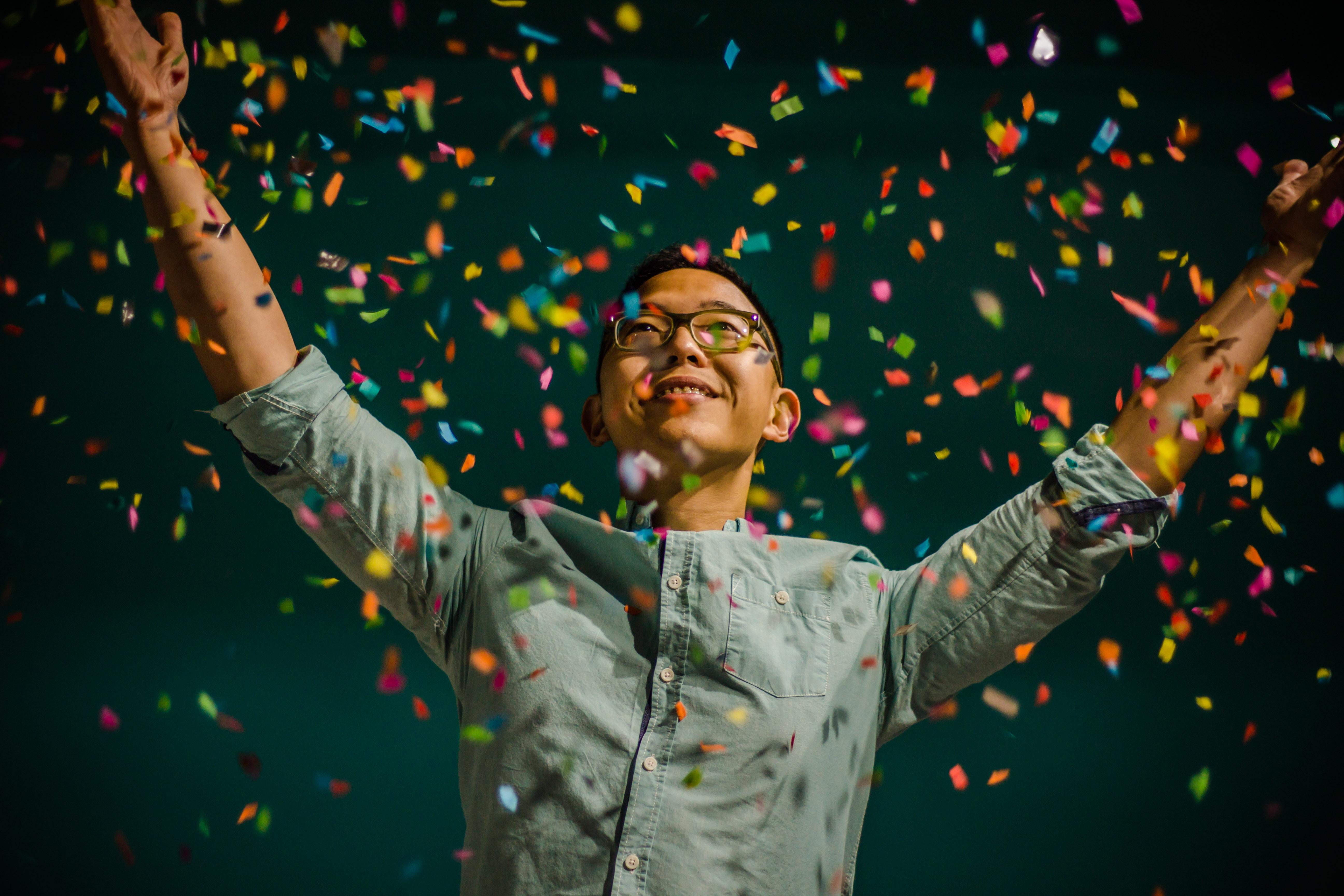 Happy person celebrates their accomplishments with colorful confetti